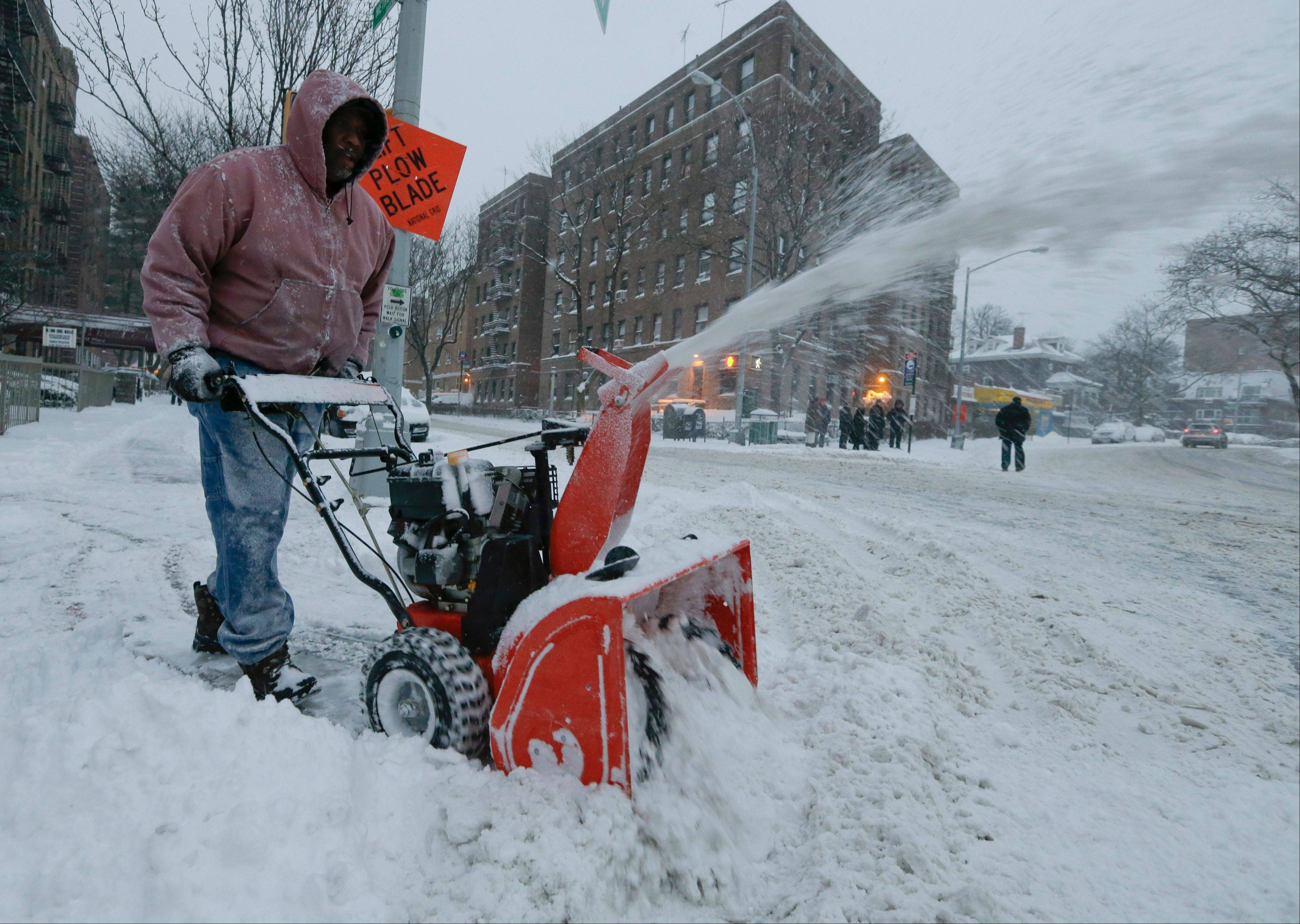 A man who did not wish to be identified uses a snowblower to clear a path Friday, Jan. 3, 2014, in New York. The New York City Office of Emergency Management issued a hazardous travel advisory into Friday, warning that roads likely would be icy and snow would continue to drift.