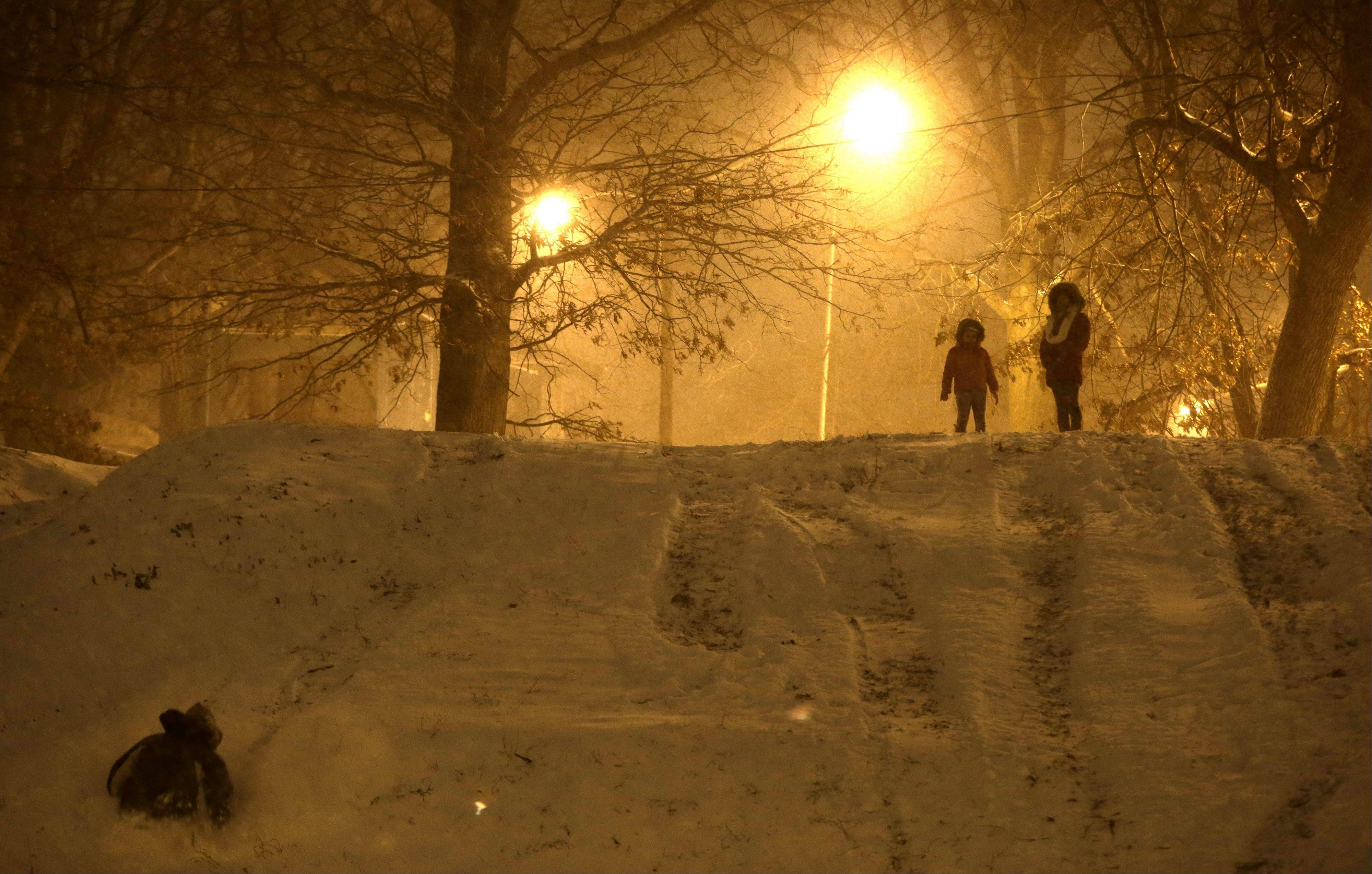 A boy, left, sleds down the hill as others look on during a late night snowfall at Leonard Gordon Park, Thursday, Jan. 2, 2014, in Jersey City, N.J. Snow and bone-chilling temperatures are expected for the overnight hours with substantial accumulation predicted.