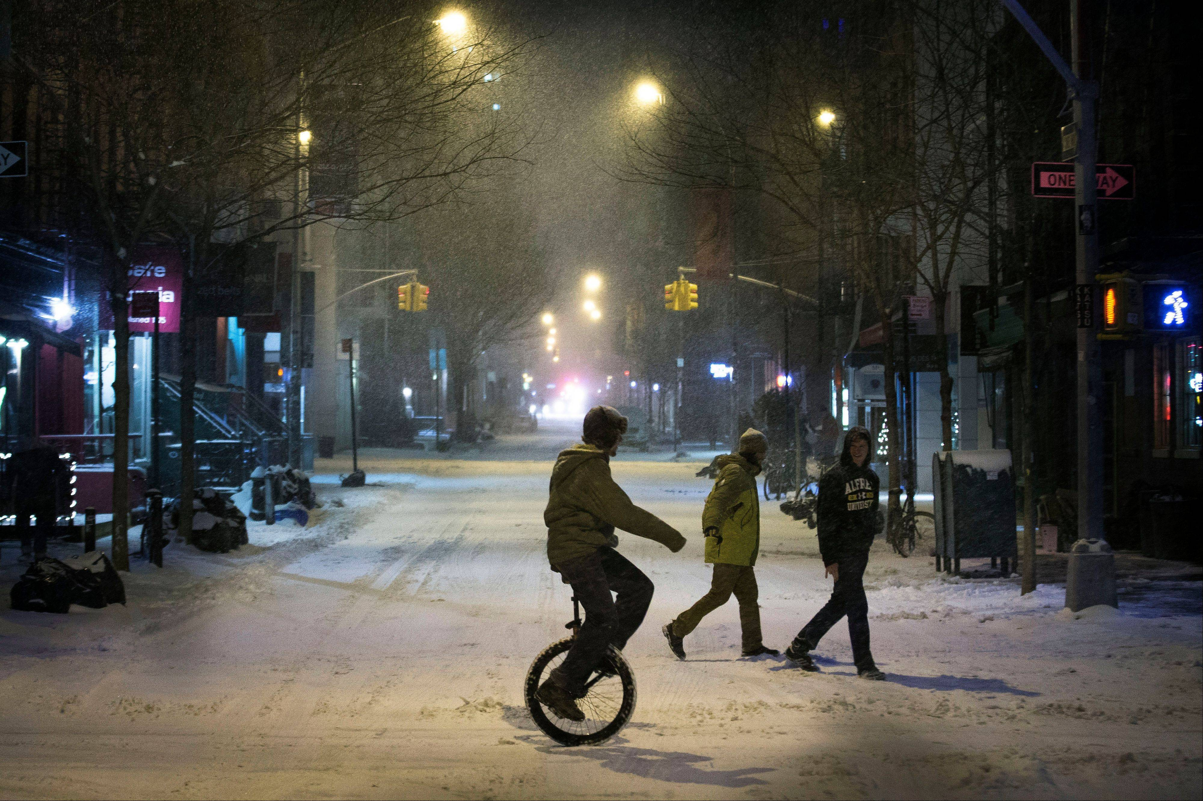 A unicyclist crosses the street during a snowstorm in the SoHo neighborhood of Manhattan, Thursday, Jan. 2, 2014, in New York. The storm is expected to bring snow, stiff winds and punishing cold into the Northeast.
