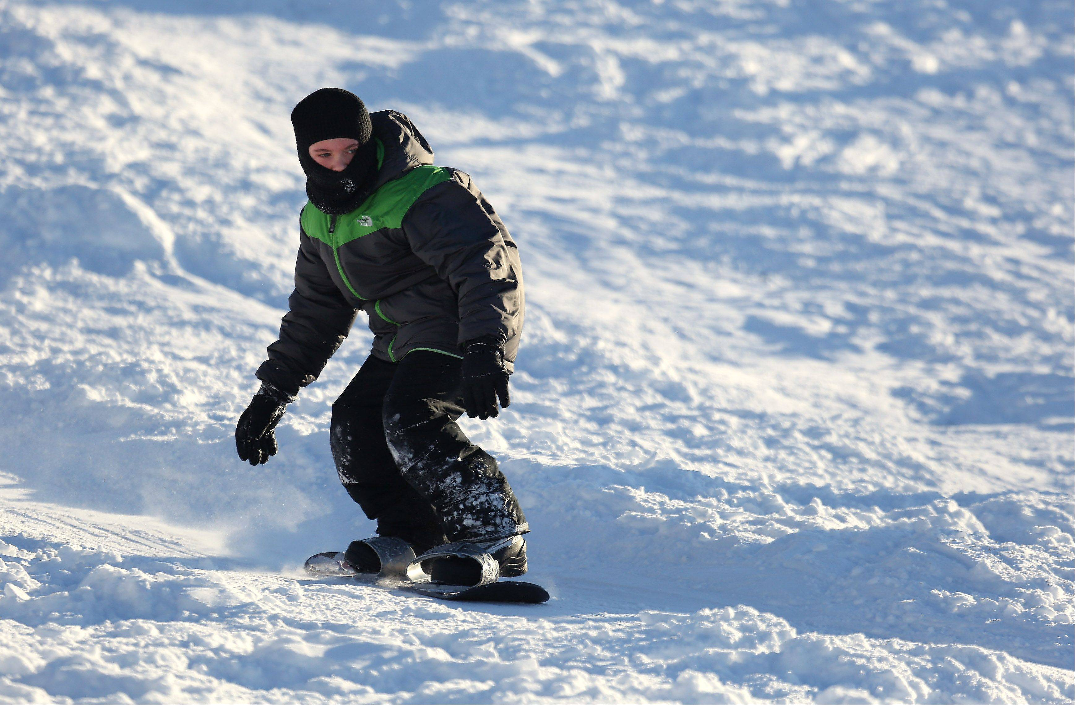 Marty Humbert, 10, rides a snowboard at Century Park in Vernon Hills on Thursday after a two-day winter storm produced almost 17 inches of snow.