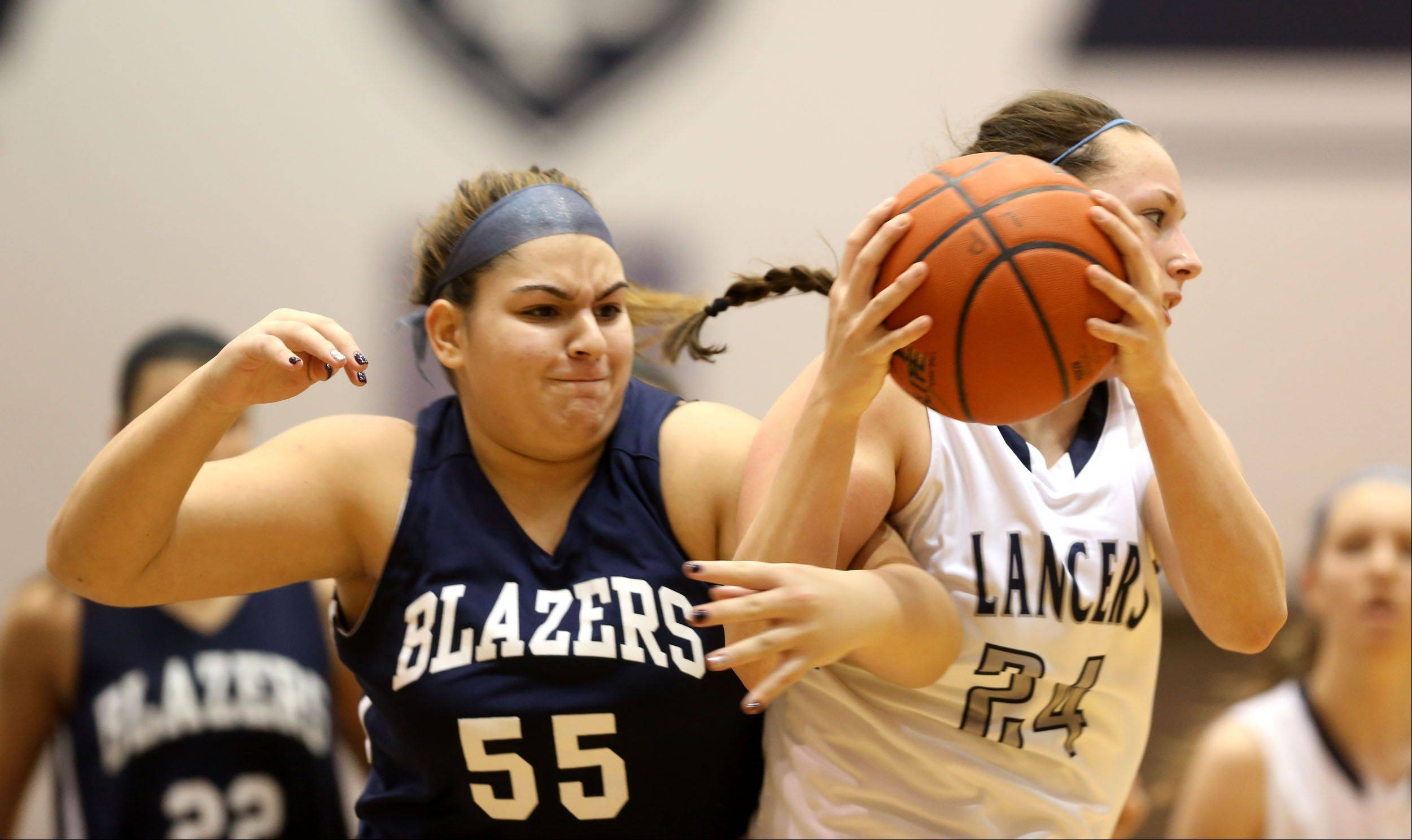 Addison Trail's Alexandar DIsilvio, left, battles Lake Park's Jen Warfield, right.