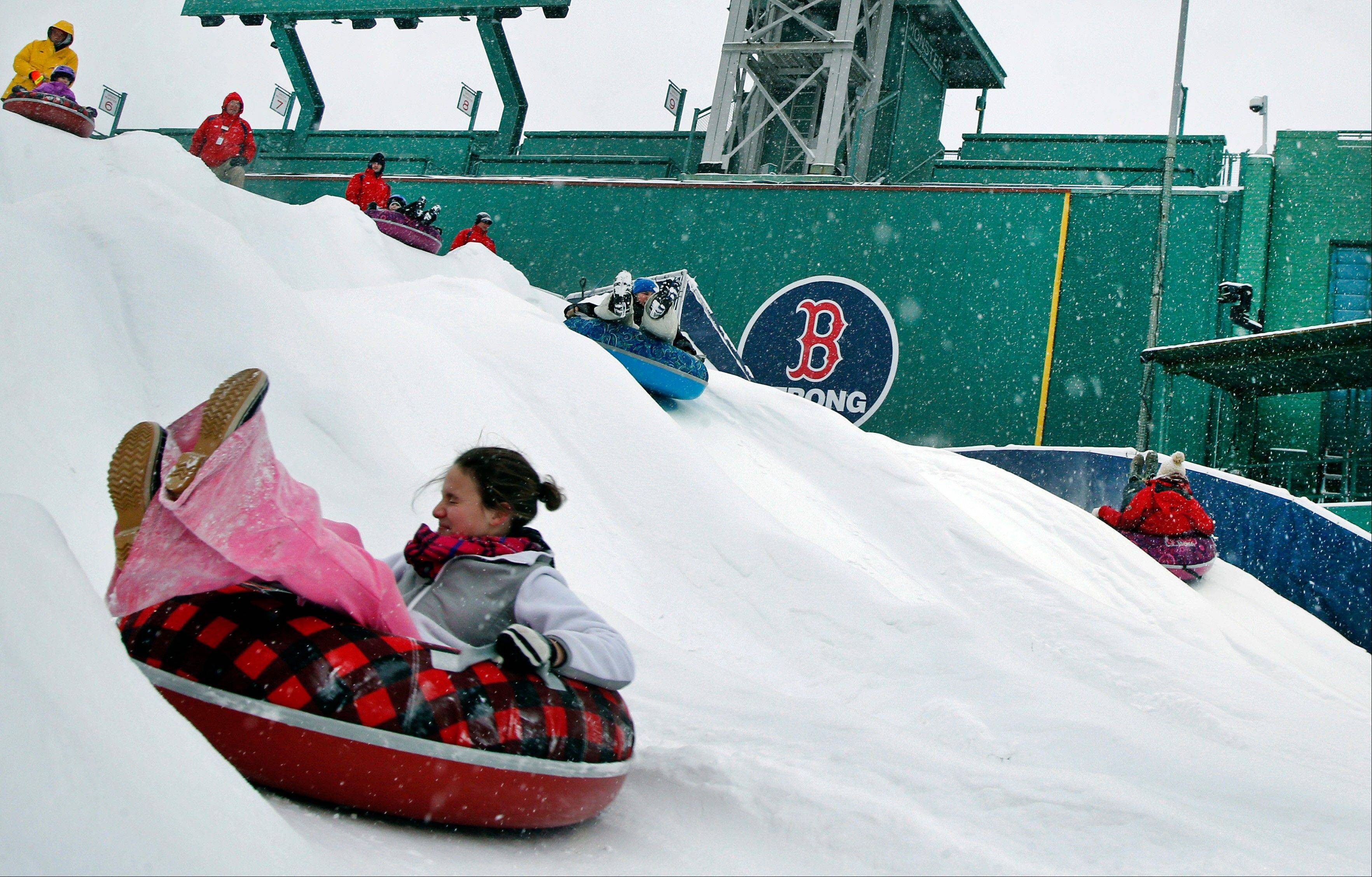 "While these kids enjoyed a slide down the ""Monster Sled"" adjacent to the left field wall as snow fell at Fenway Park in Boston on Thursday, the heavy snowfall forced stadium operators to cancel an outdoor hockey game scheduled there."