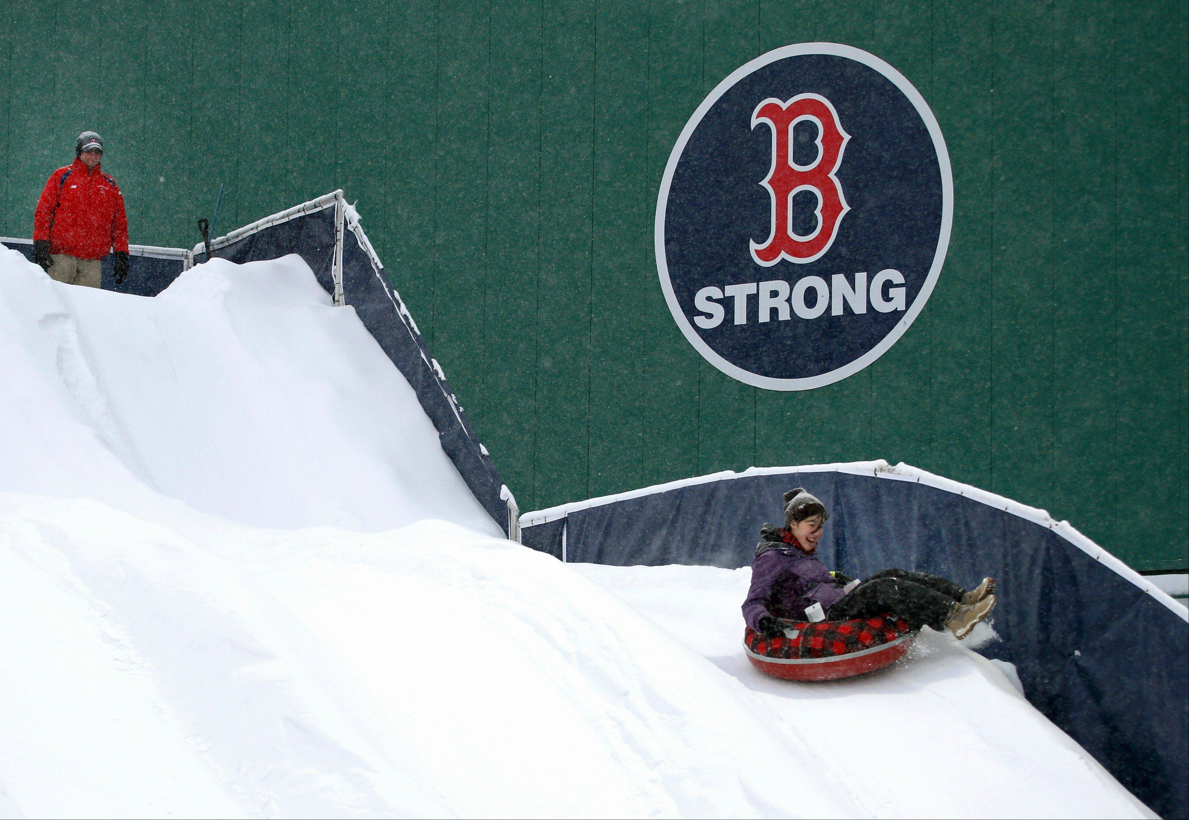 "A tuber enjoys a slide down the ""Monster Sled"" adjacent to the left field wall at Fenway Park in Boston on Thursday. More than a foot of snow fell in Boston, forcing massive cancellations. Among the casualties was an outdoor hockey game between Northeastern and Harvard at Fenway Park."