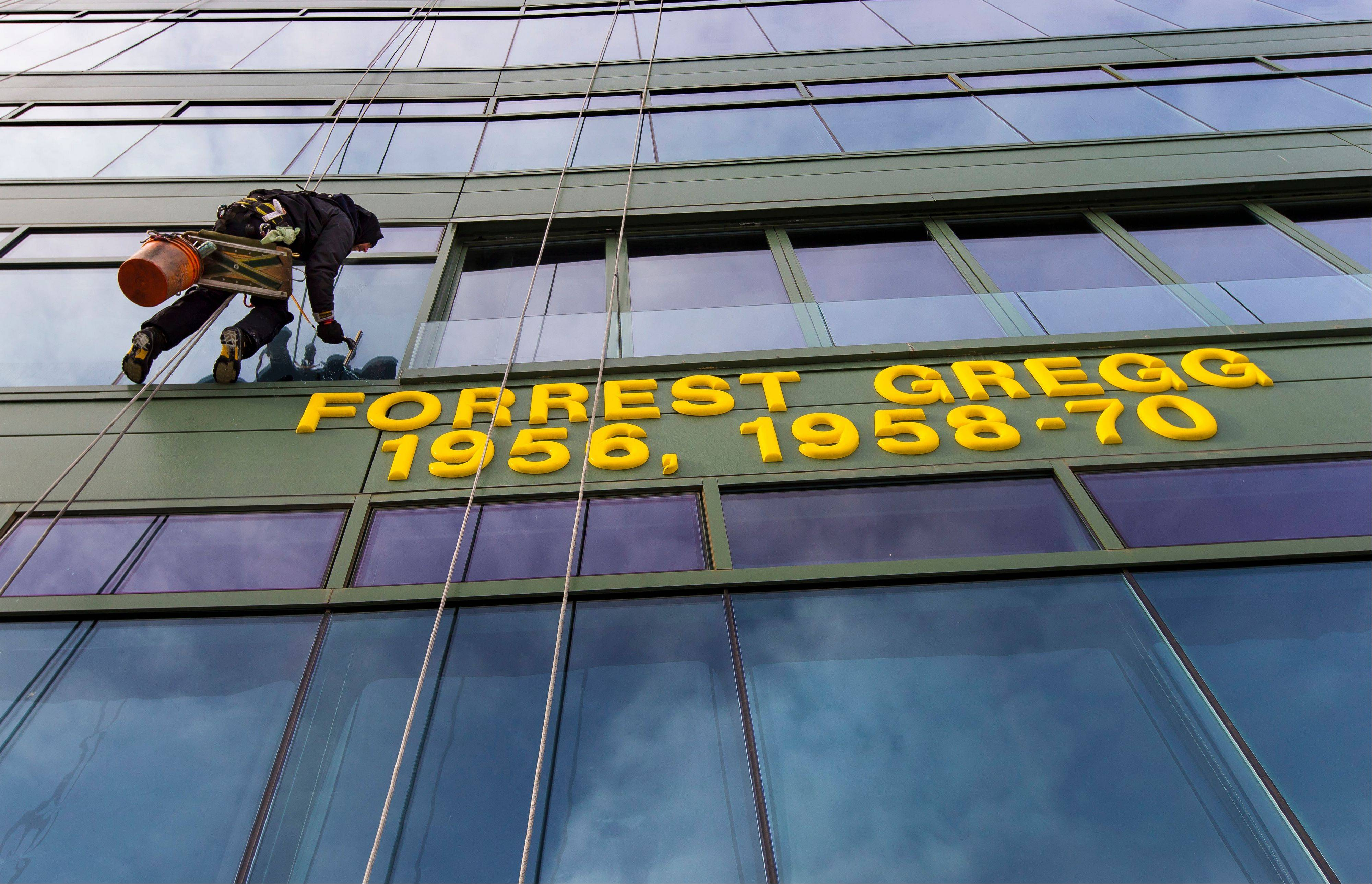 Jeff Anderson cleans the windows Friday on the sky boxes at Lambeau Field in Green Bay, Wis.