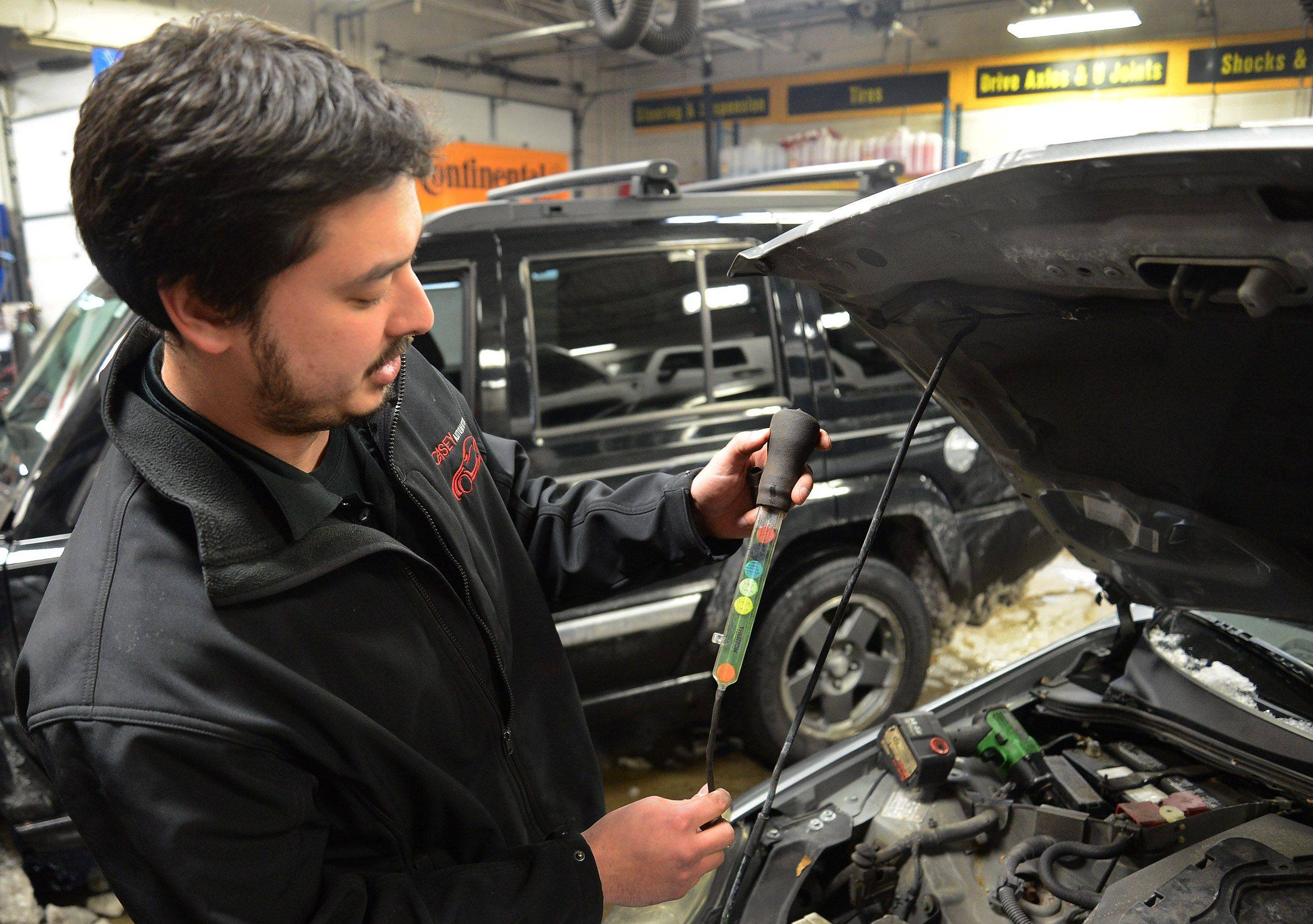 Store manager Paul Casey checks the antifreeze in a car at Casey Automotive in Arlington Heights.