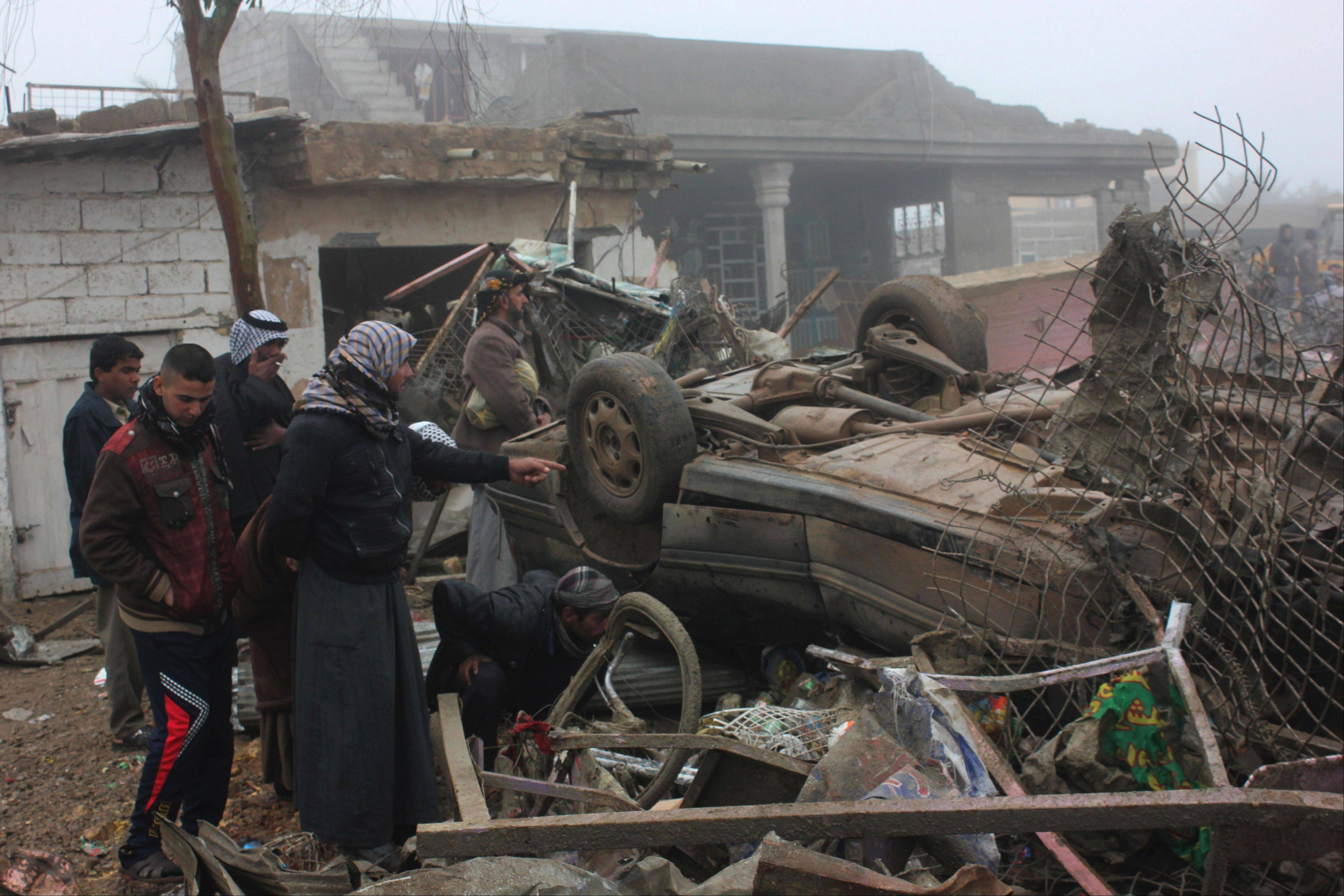 Civilians inspect the aftermath of a massive bomb attack Friday in Balad Ruz, 45 miles northeast of Baghdad. Officials say scores were killed when a pickup truck laden with explosives blew up on a busy commercial street Thursday evening.