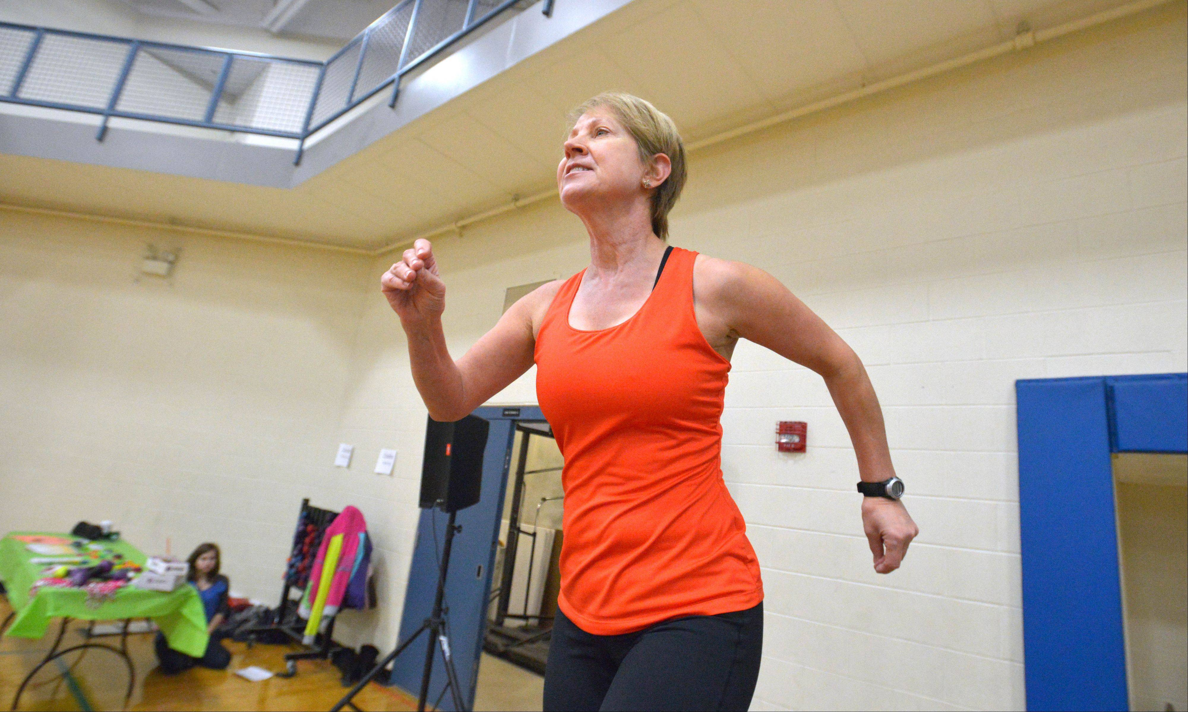 Total Fitness instructor Alice Lively attempts to get the crowd moving during the health and resource fair at the Wood Dale Park District building Saturday.