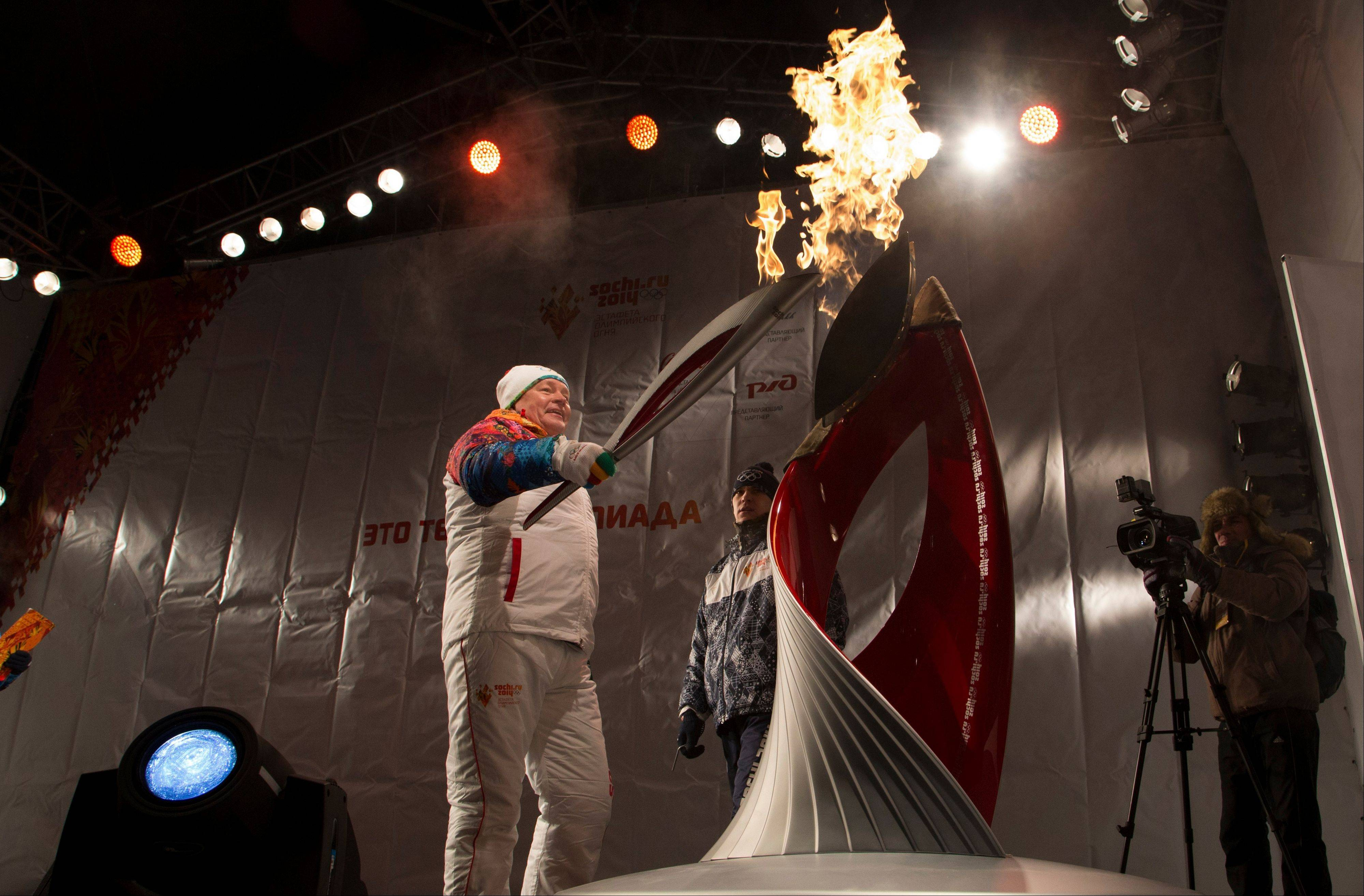 Olympic torch bearer Viktor Basargin holds the Olympic torch Saturday as he lights a symbolic Olympic flame during the torch relay in Perm, Russia.