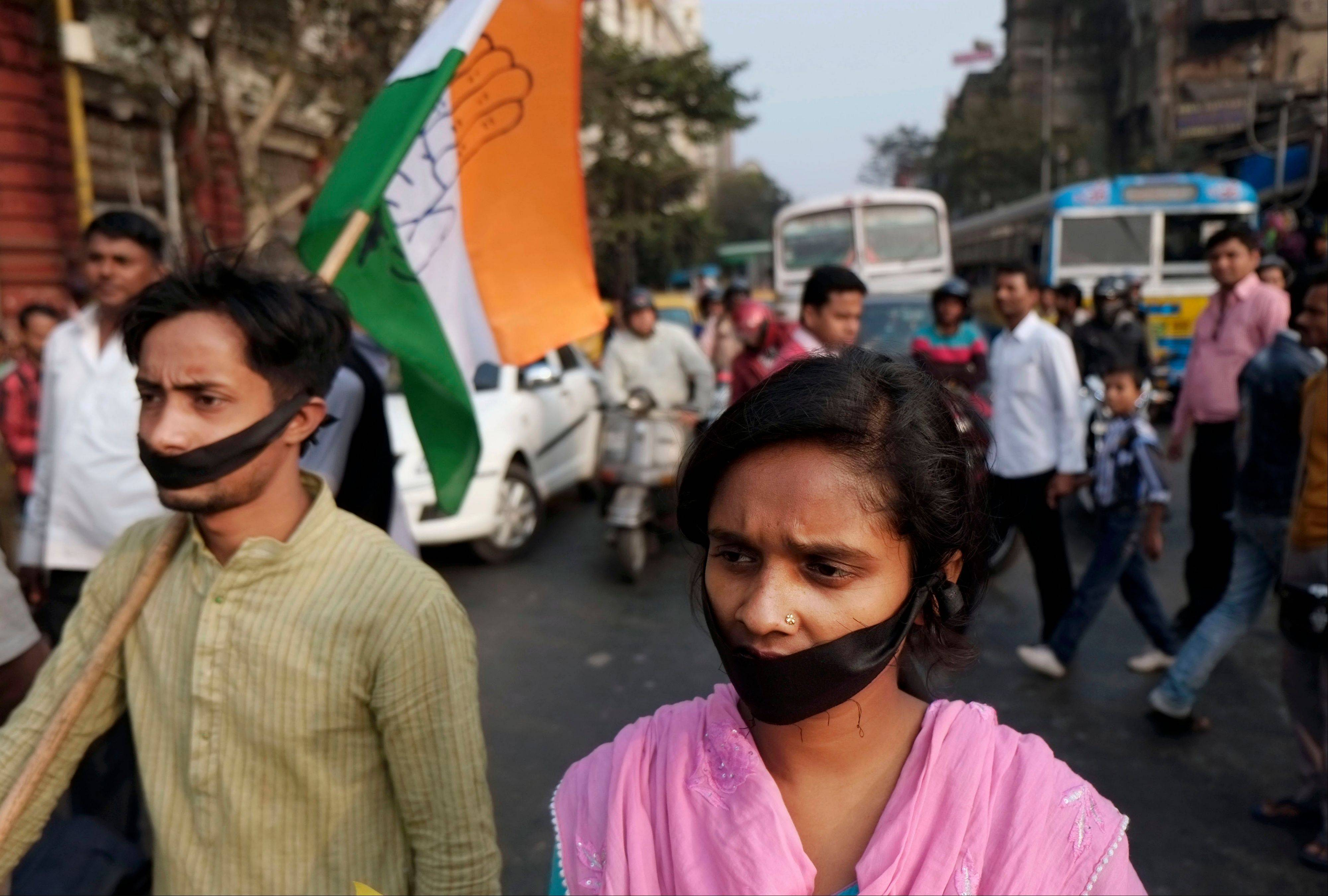 Activists of Indian National Congress with black bands around their mouth block traffic during a protest against a gang-rape and murder of a 16-year-old girl at Madhyamgram, about 16 miles north of Kolkata, India, Friday, Jan. 3. On Dec. 31 the girl was set on fire and died due to burn injuries after being raped twice in October. The death of the girl has sparked outrage in the metropolis.