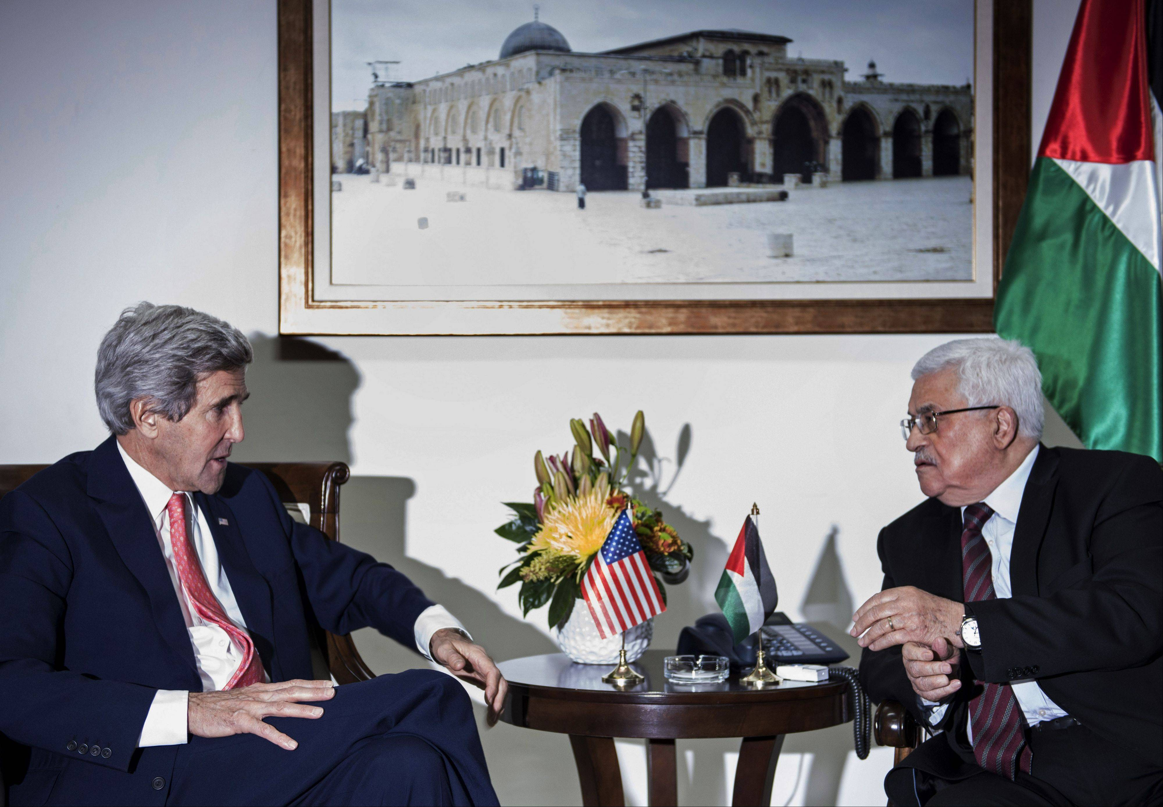 Associated Press U.S. Secretary of State John Kerry, left, and Palestinian President Mahmoud Abbas talk before a meeting at the presidential compound in the West Bank city of Ramallah on Friday, Jan. 3. Kerry took the tenth trip to the region to negotiate a peace deal he claims is �not mission impossible.�