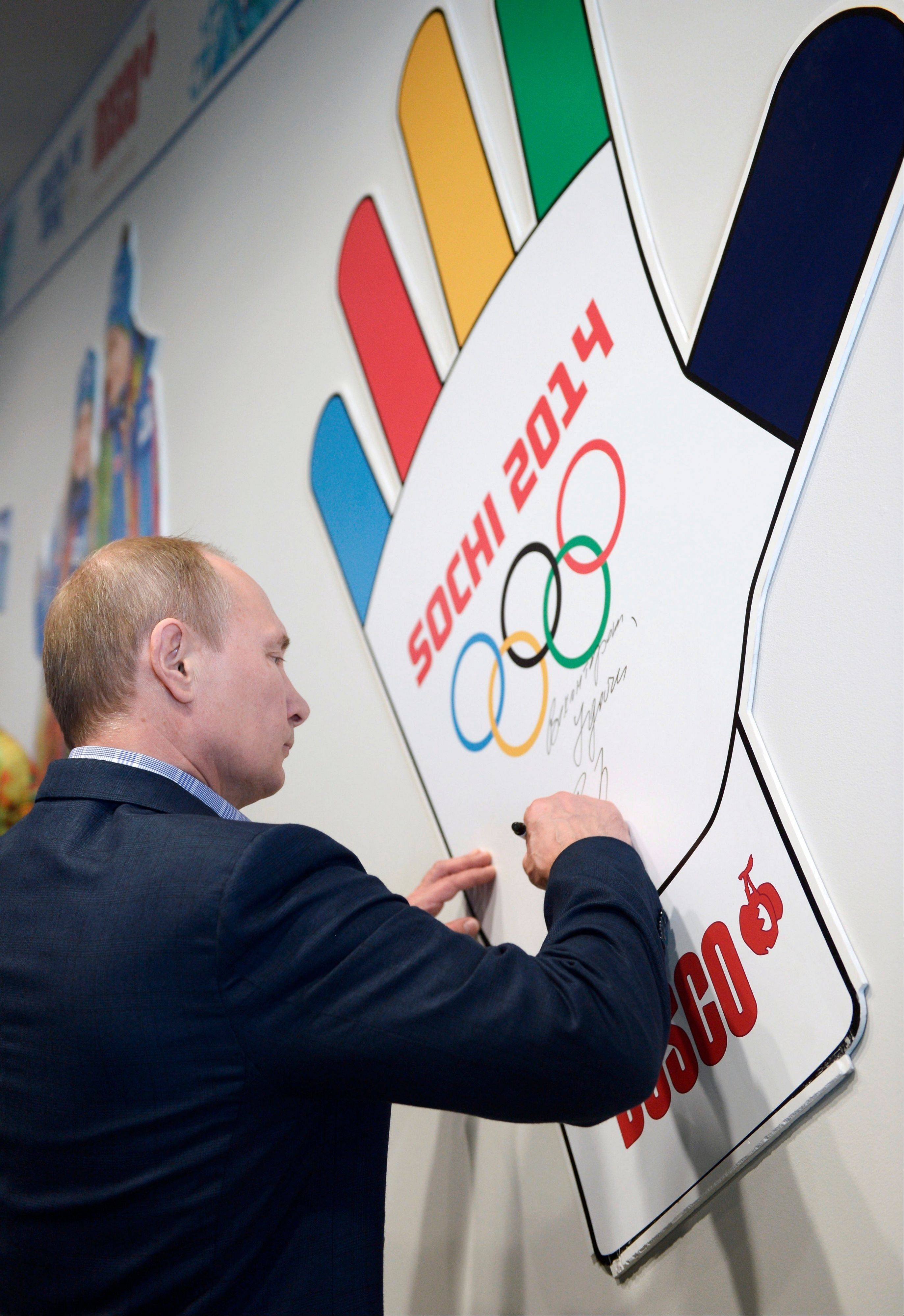 Russian President Vladimir Putin signs his name during a visit to the training center for volunteers for the Winter Olympics at the Black Sea resort of Sochi, southern Russia, Saturday, Jan. 4. Putin has rescinded a blanket ban on demonstrations in Sochi in and around the Winter Olympics and Paralympics.