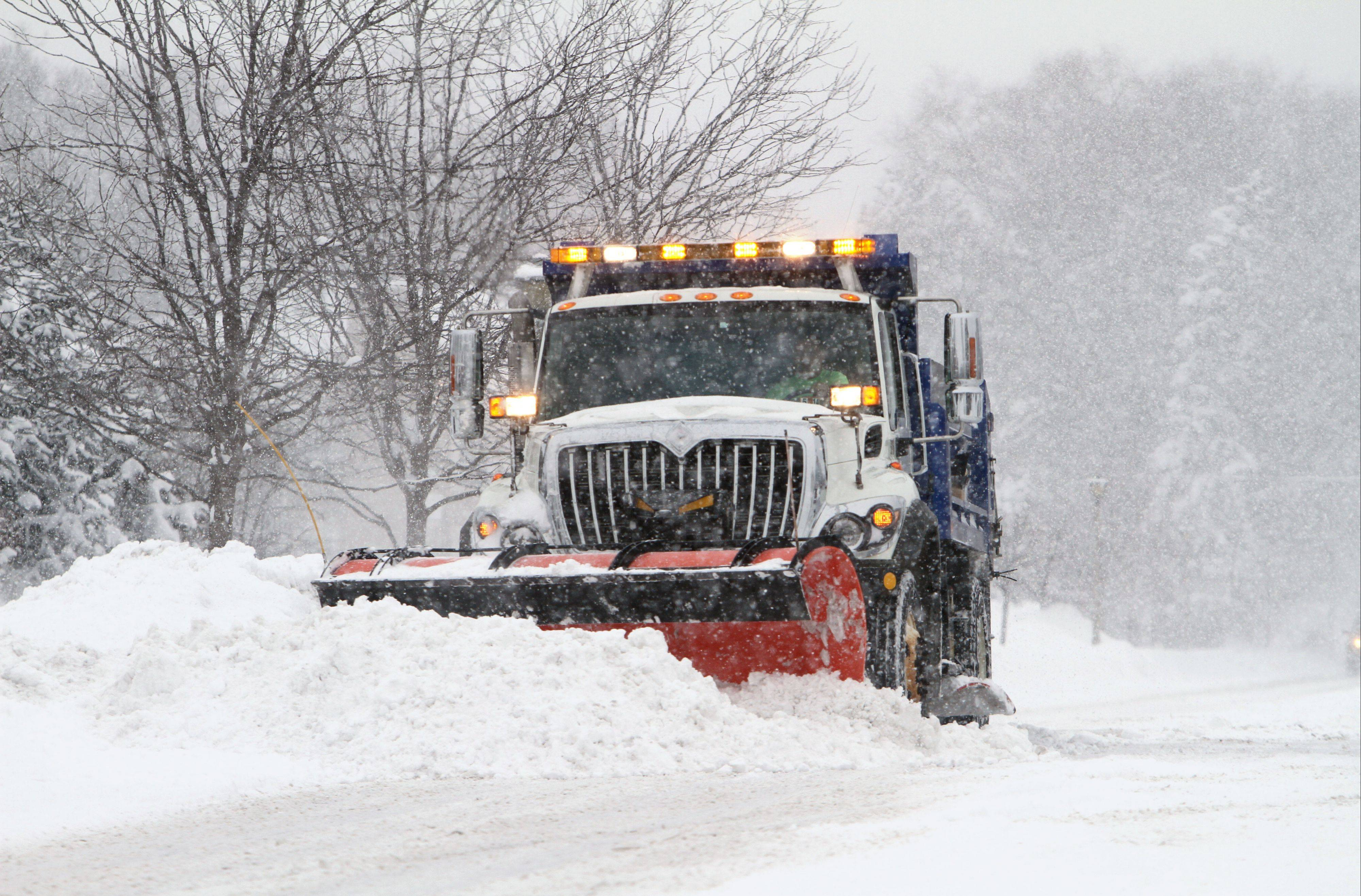 A snowplow makes its way down Garfield Avenue in Libertyville Thursday morning after a winter storm dumped over a foot of snow in the area. Several towns are feeling a budget squeeze after so much snow so early.