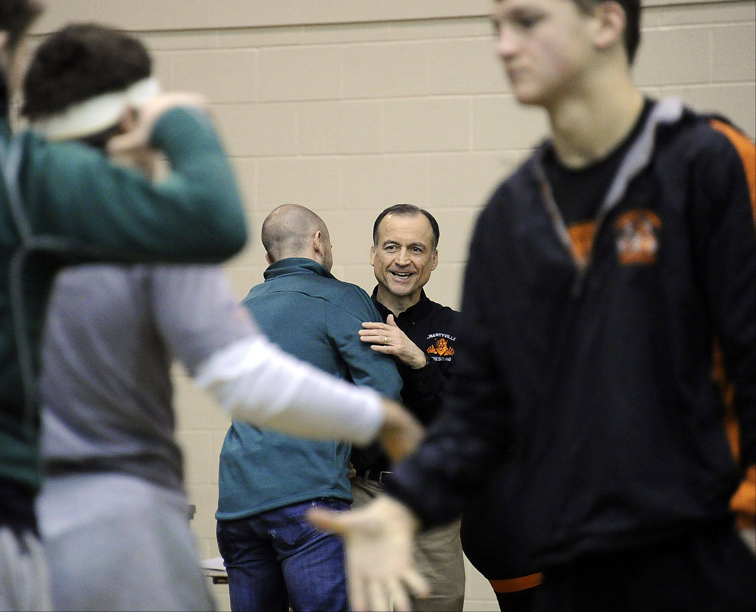 Libertyville wrestling coach Dale Eggert is congratulated by the coaching staff of Crystal Lake South after the Wildcats defeated the Gators in Saturday�s quad at Schaumburg. Eggert�s team later topped Naperville Central and Schaumburg, giving him 500 career coaching triumphs.