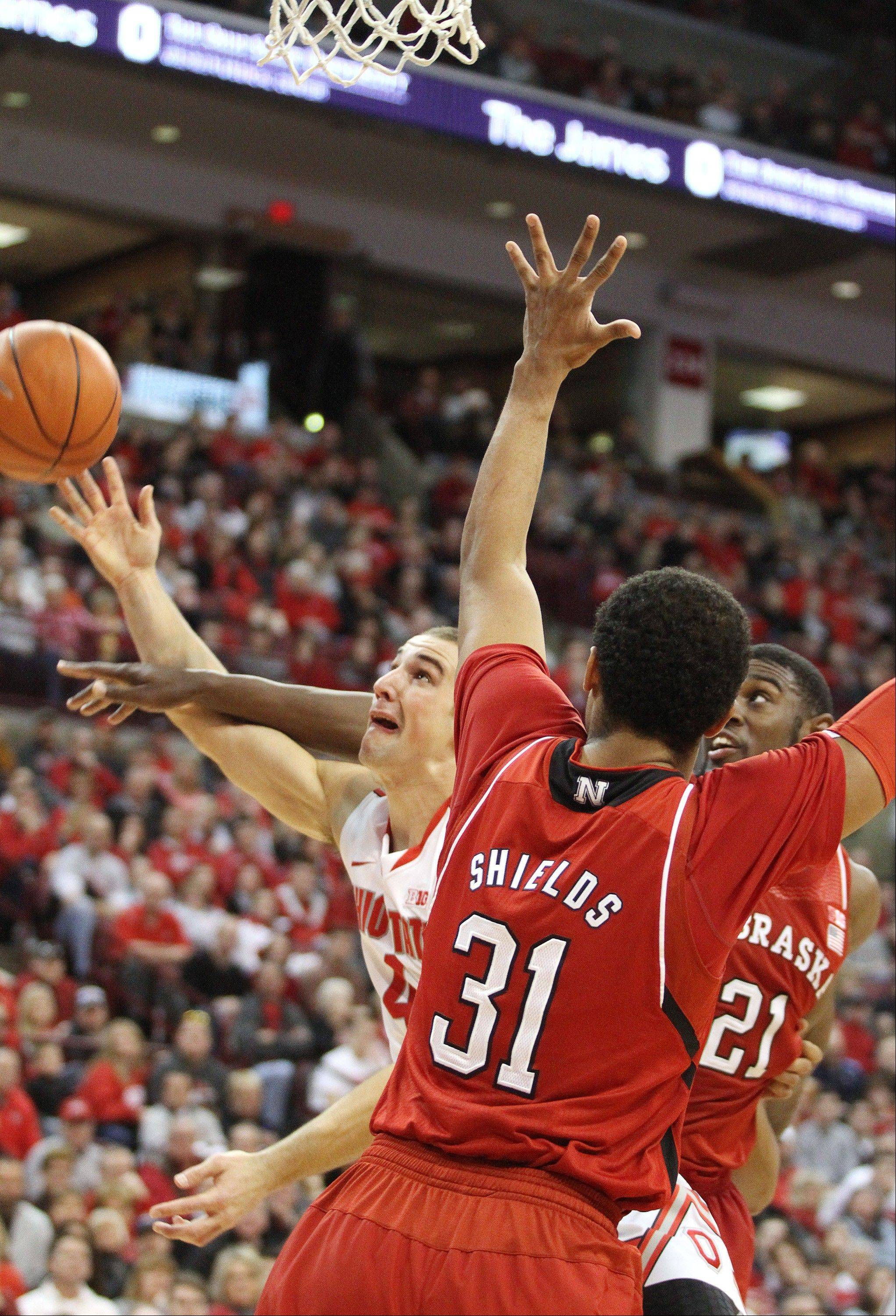 Ohio State's Aaron Craft, left, is fouled by Nebraska's Leslee Smith (21) during the first half of an NCAA college basketball game Saturday, Jan. 4, 2014, in Columbus, Ohio. Nebraska's Shavon Shields (31) defends on the play. (AP Photo/Mike Munden)
