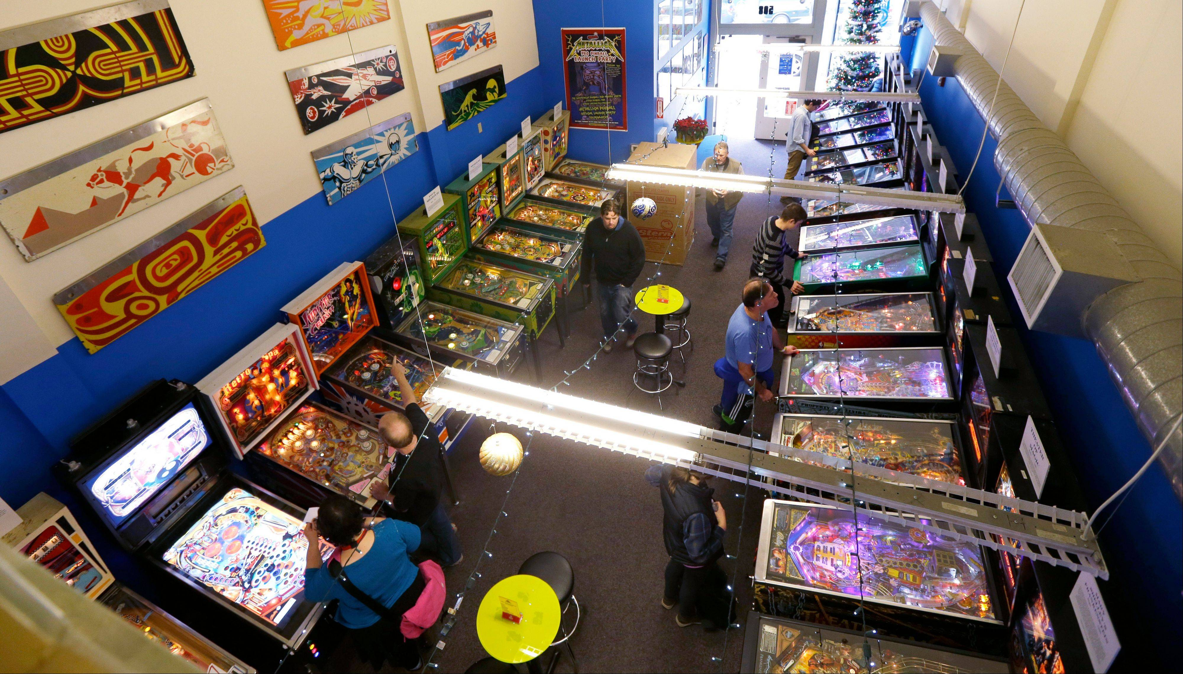 Modern pinball machines line the wall at right while older models sit on the left at the Seattle Pinball Museum. The museum allows visitors who pay the admission fee to play unlimited rounds on the machines.