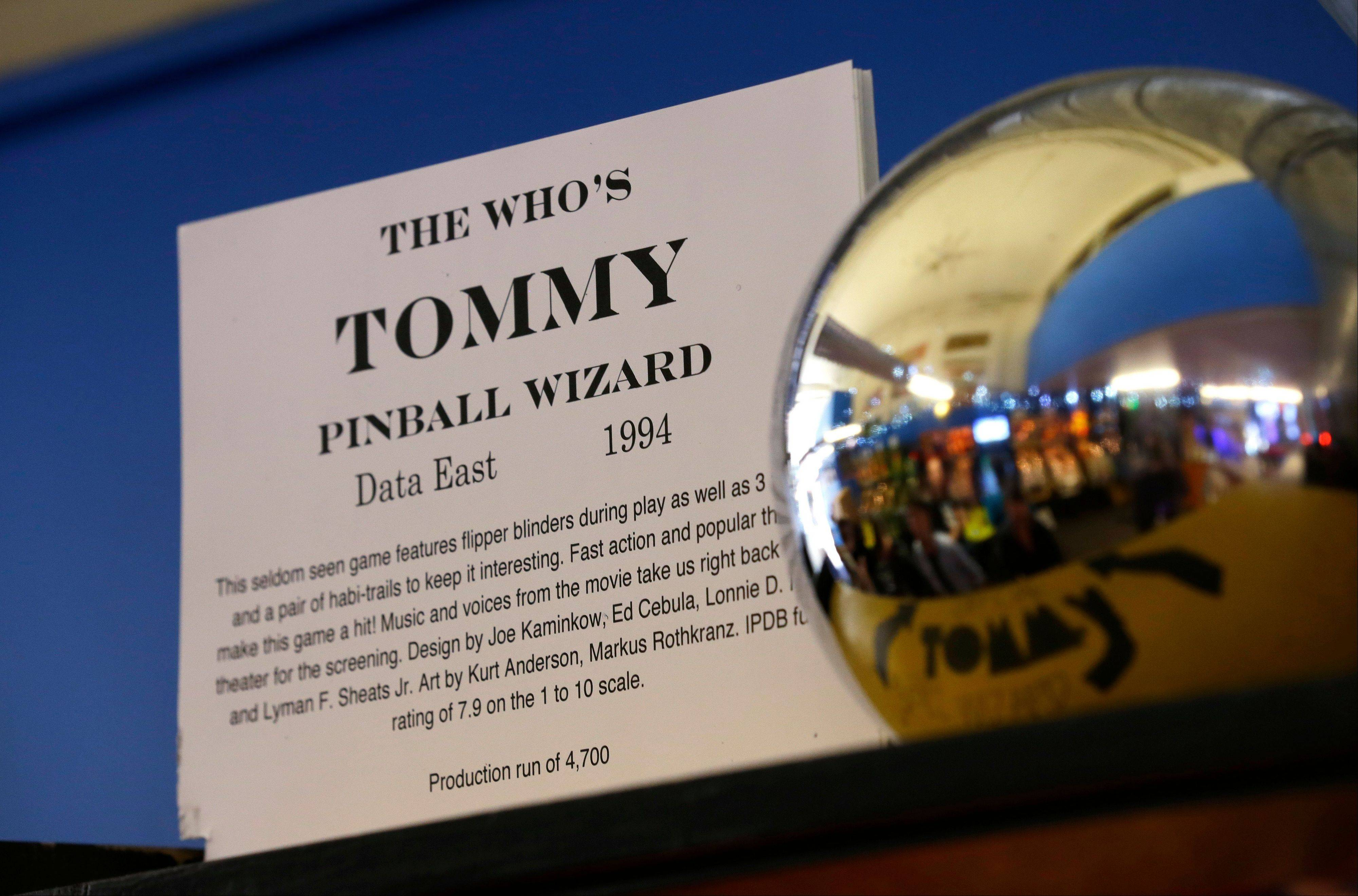 The 1994 The Who's Tommy pinball machine is on display near a giant pinball at the Seattle Pinball Museum.