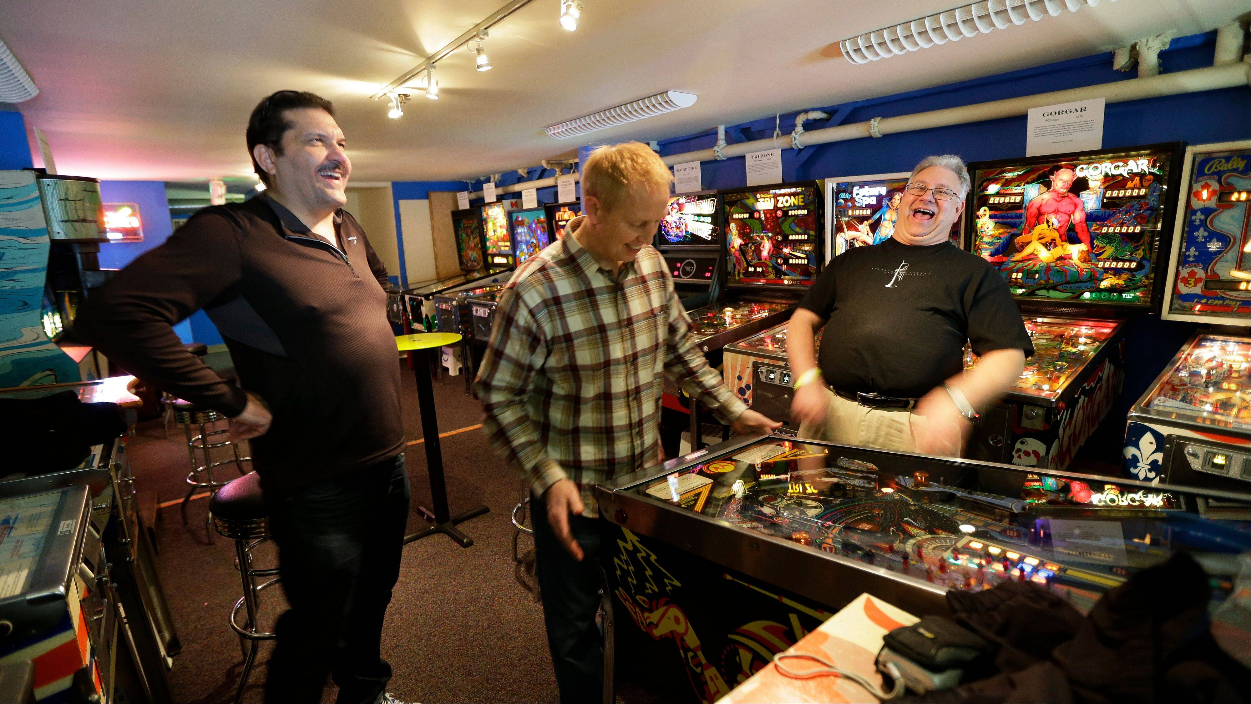 Out-of-state visitors Jeff Goldsmith, left, Jim Lindquist and Dave Socha play the PIN BOT pinball machine, which was released in 1986, as they visit the Seattle Pinball Museum.