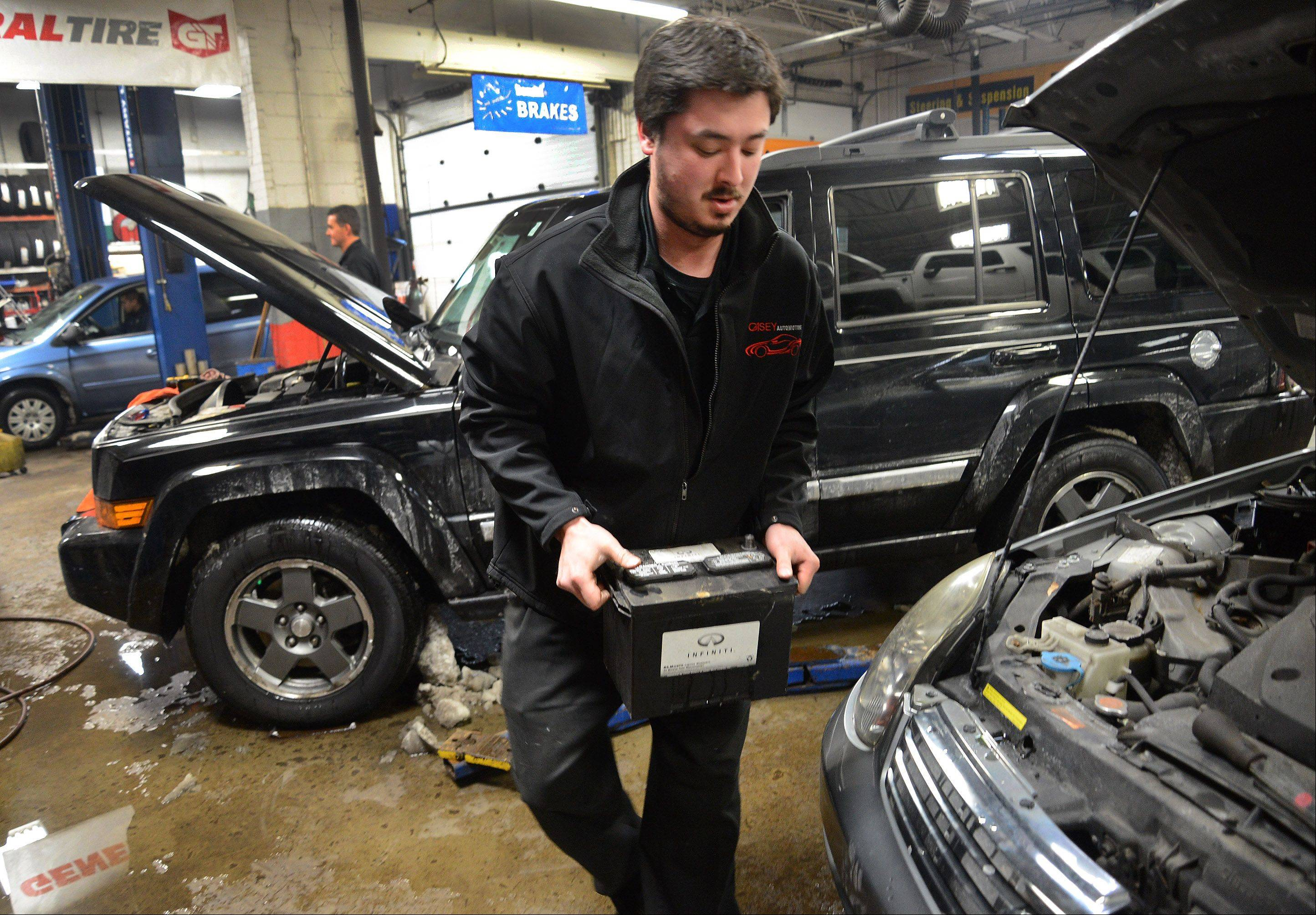 Store manager Paul Casey replaces a dead battery in a car at Casey Automotive in Arlington Heights. Older batteries don't do well in frigid weather.
