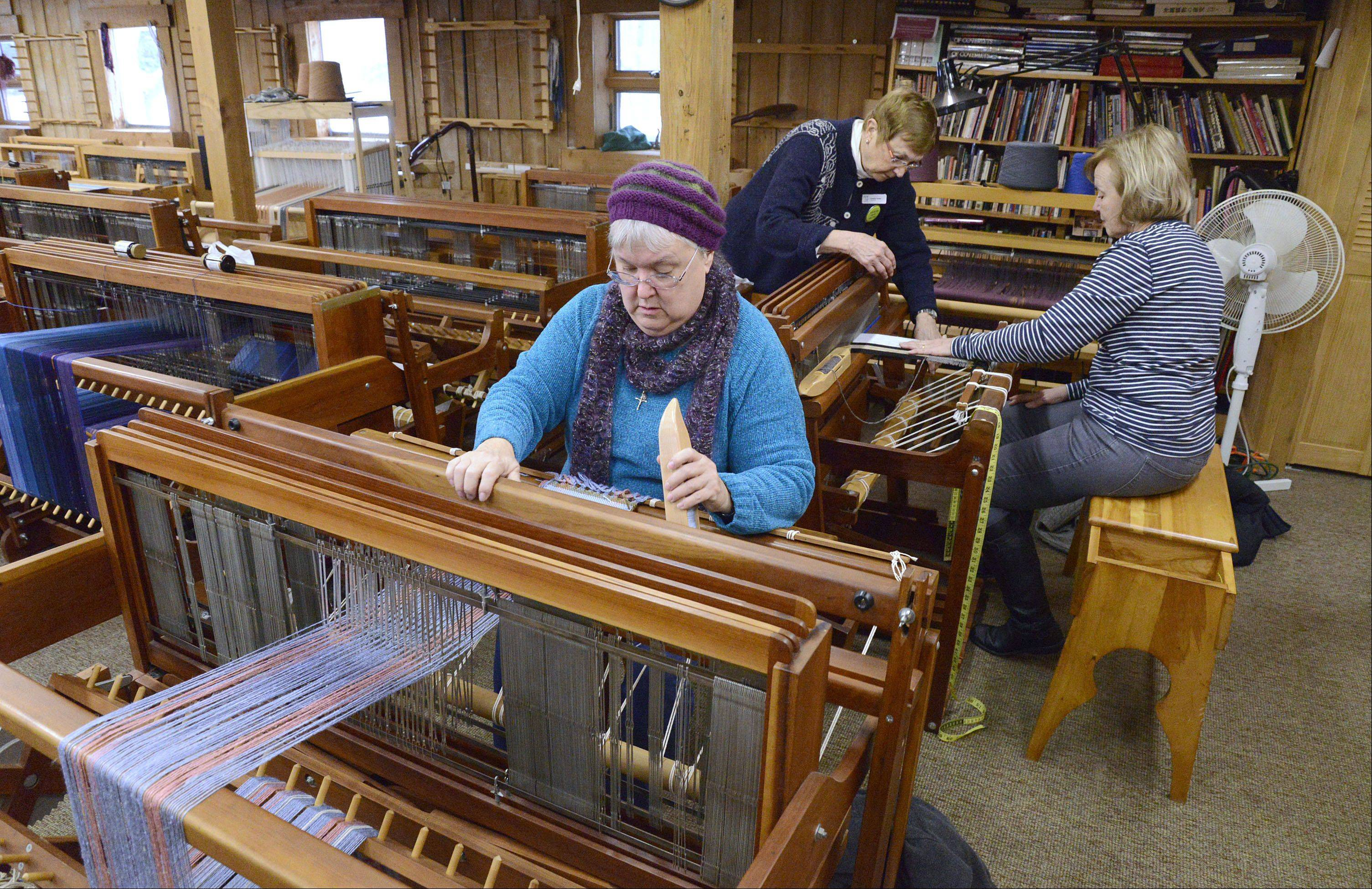 Pam Hirsch of Algonquin, front, and Ann Sutherland of Winfield learn how to weave on looms with the help of Fine Line Creative Arts Center volunteer Louise Ioder of Elburn Saturday. Ioder has been a volunteer at the St. Charles center for close to 15 years.