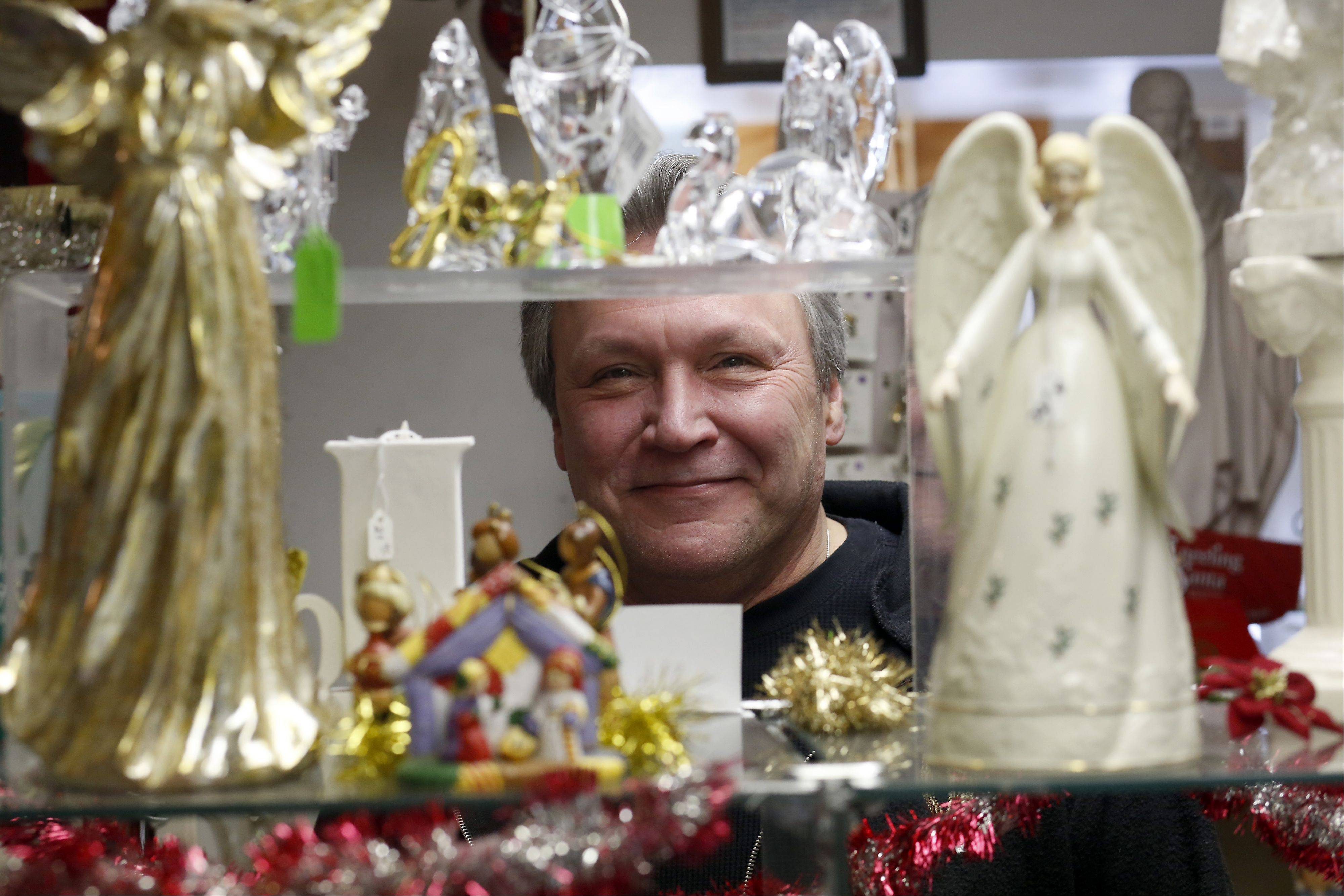 Seen through a host of angel figurines is Michael Kulpin, the operator of Angel Kisses in St. Charles.