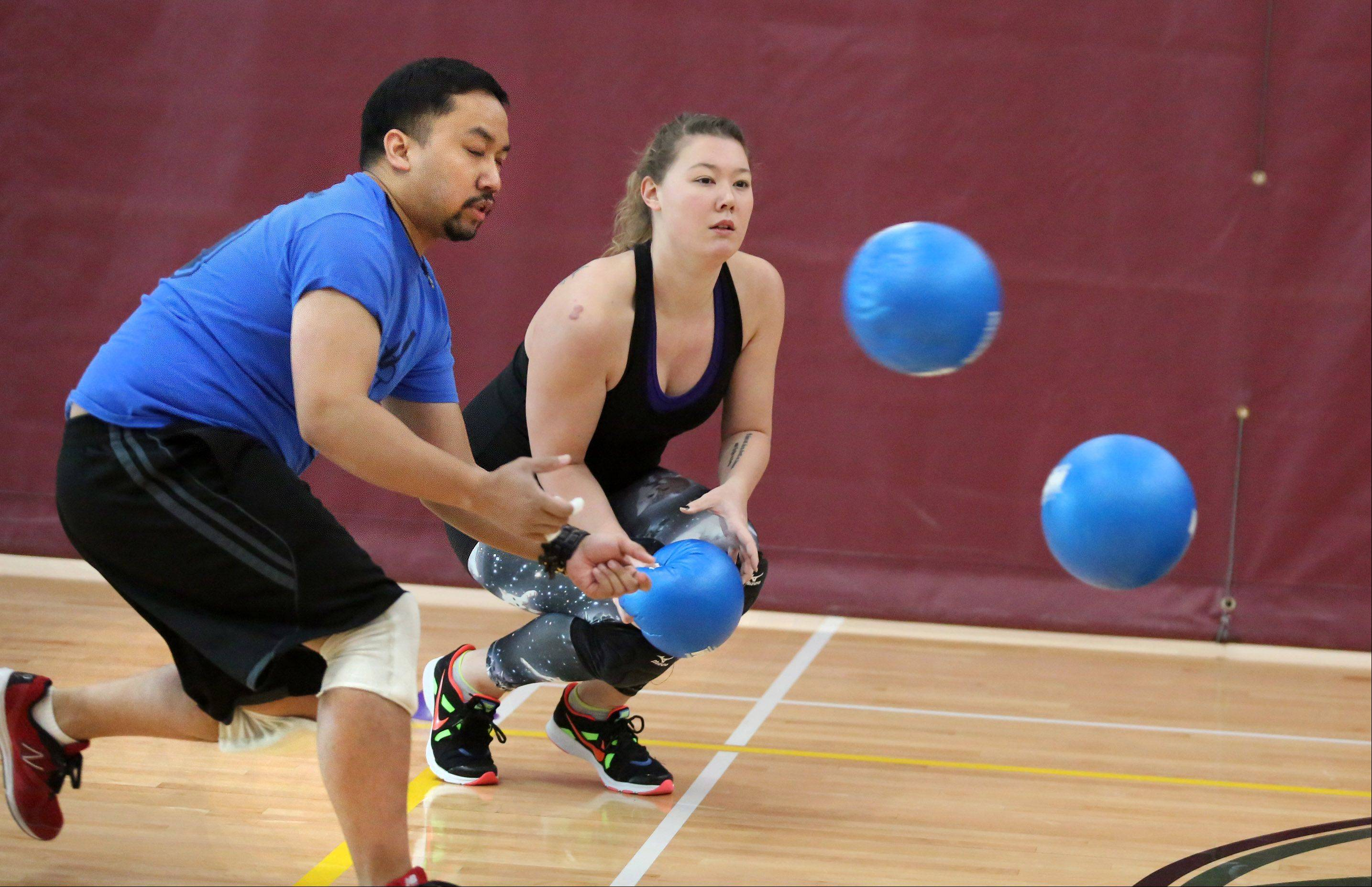Kat Takeda of Elk Grove Village and Jason Rejoano of Wheeling on Team Chakes dodge two balls before Takeda throws the ball during adult dodgeball championships in the National Amateur Dodgeball Association Winter Nationals at the Sport Center on Saturday in Schaumburg.