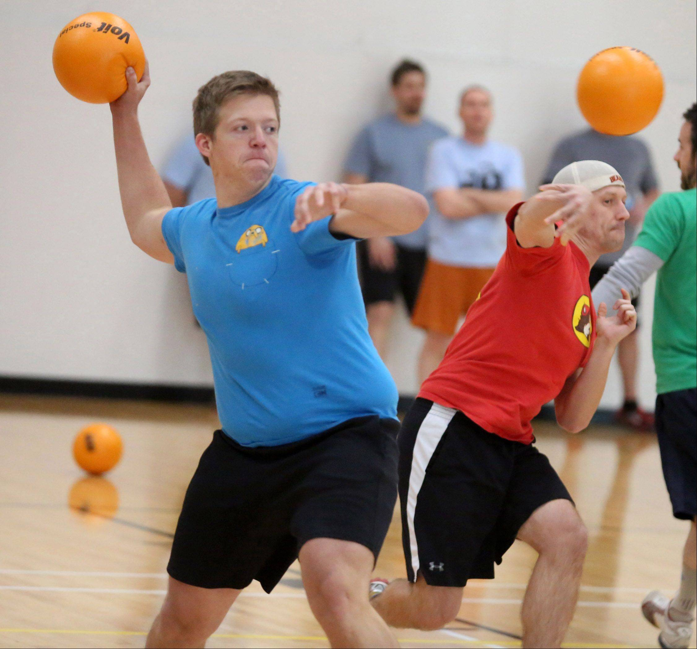 George LeClaire/gleclaire@dailyherald.comDavid Pinkawa of Des Plaines and Greg Putra of Lisle with Out Of Shape Cobras looks for members of the team they are competing against to throw at during adult dodgeball championships Saturday in Schaumburg.