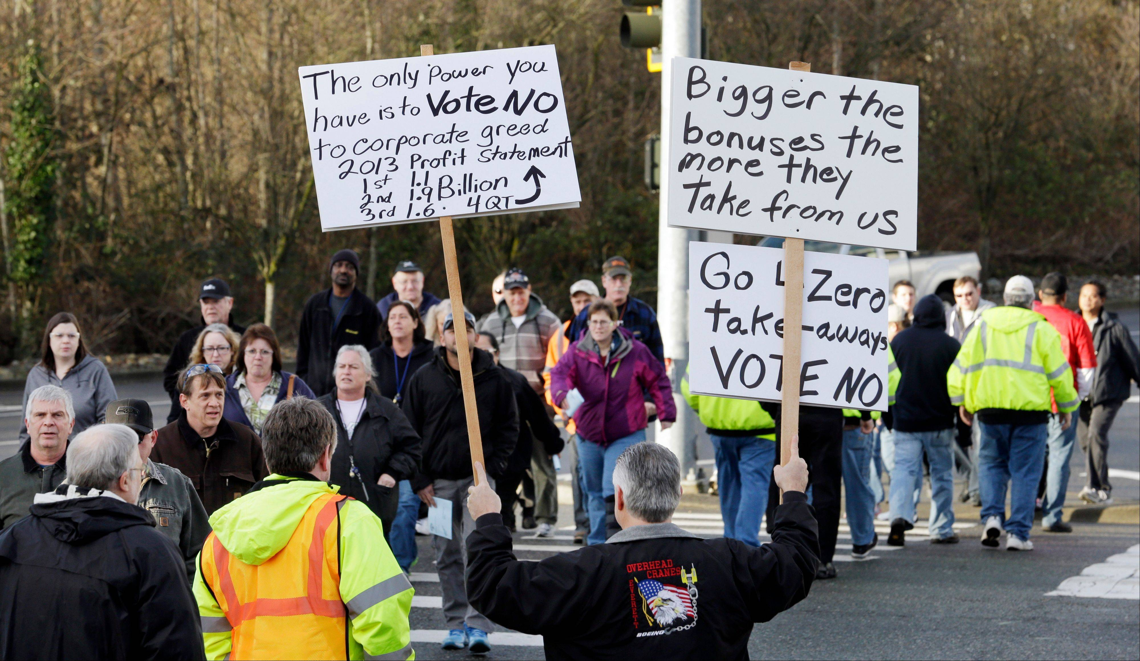 "Boeing machinist Eddie Bjorgo greets fellow workers heading to a union hall Friday to cast ballots with signs urging a ""no"" vote, in Everett, Wash."