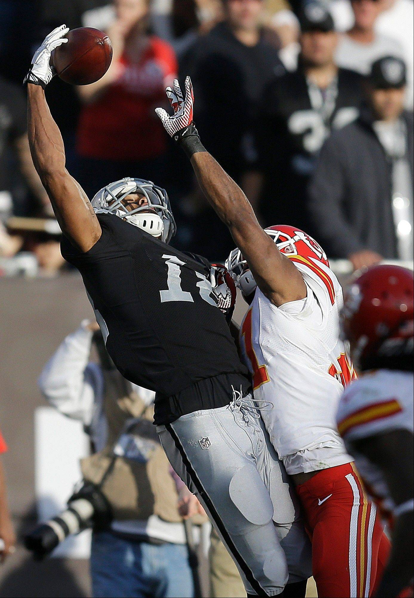 Oakland Raiders wide receiver Andre Holmes, left, catches a pass over Kansas City Chiefs cornerback Marcus Cooper during the third quarter of an NFL football game in Oakland, Calif., Sunday, Dec. 15, 2013.