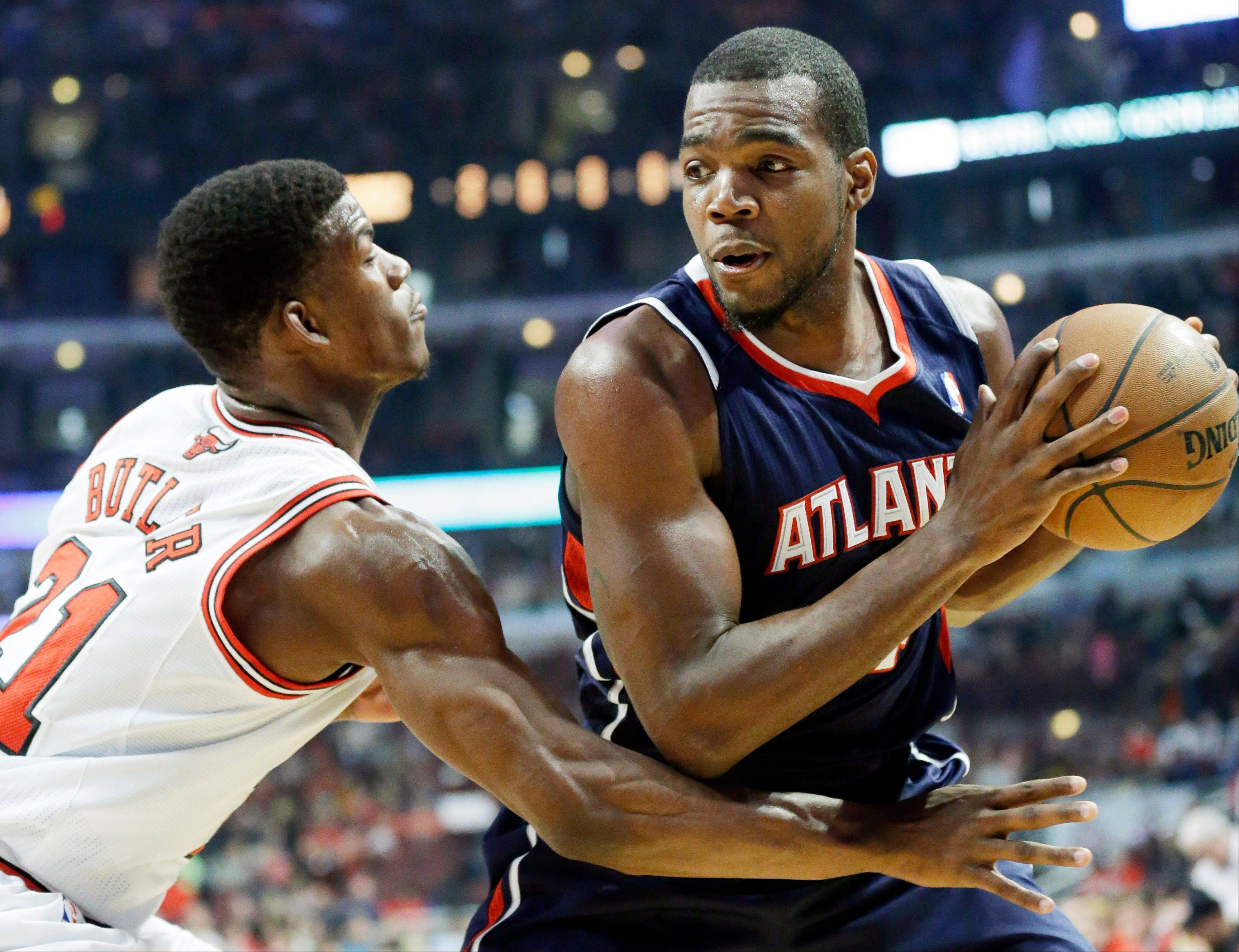 Bulls guard Jimmy Butler sticks close to Hawks forward Paul Millsap as Millsap looks to pass during the Bulls' victory Saturday night.