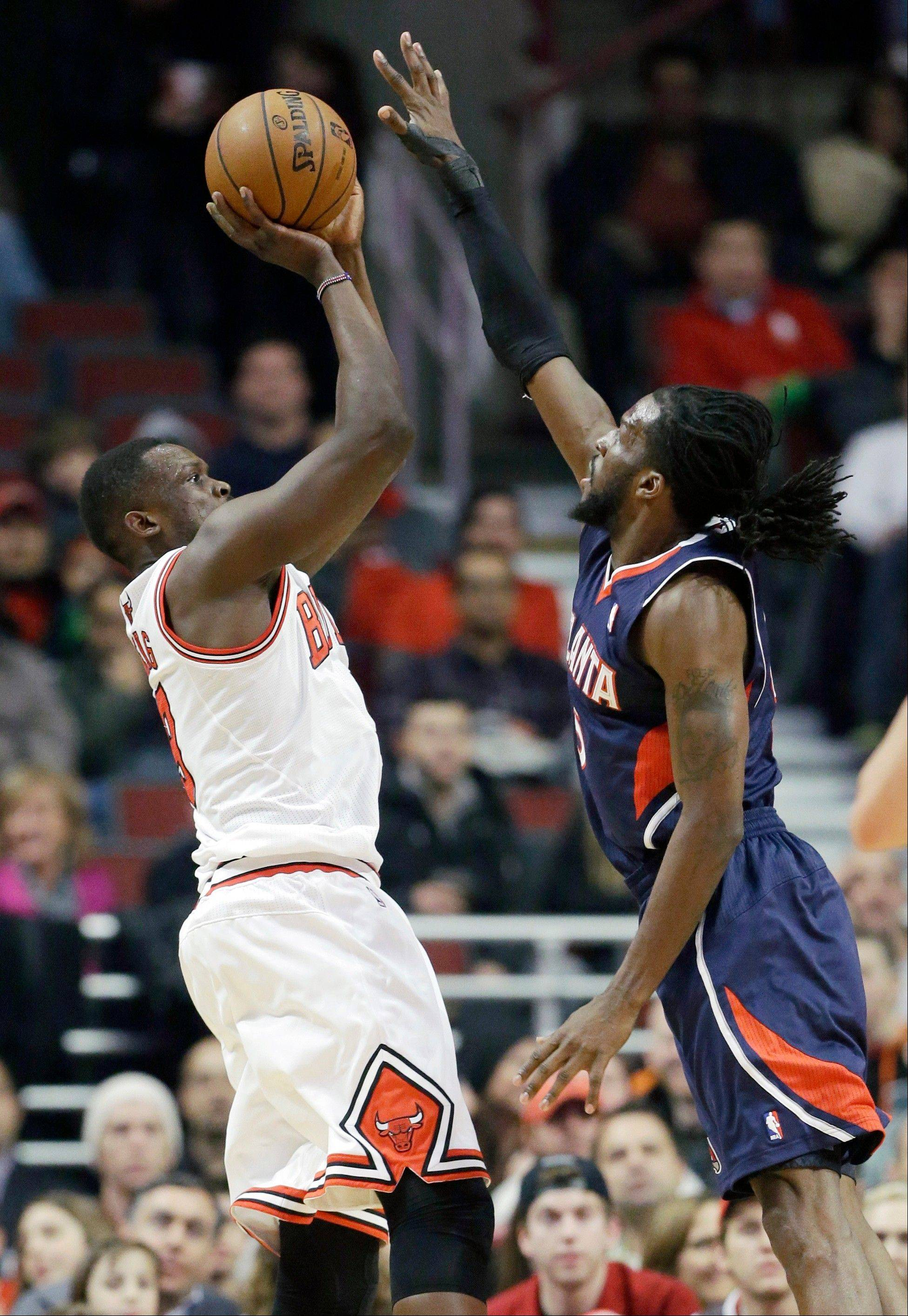Bulls forward Luol Deng, left, shoots over Atlanta Hawks forward DeMarre Carroll during Saturday night's game at the United Center. Deng scored 17 points in the Bulls' 91-84 win over the Atlanta Hawks.