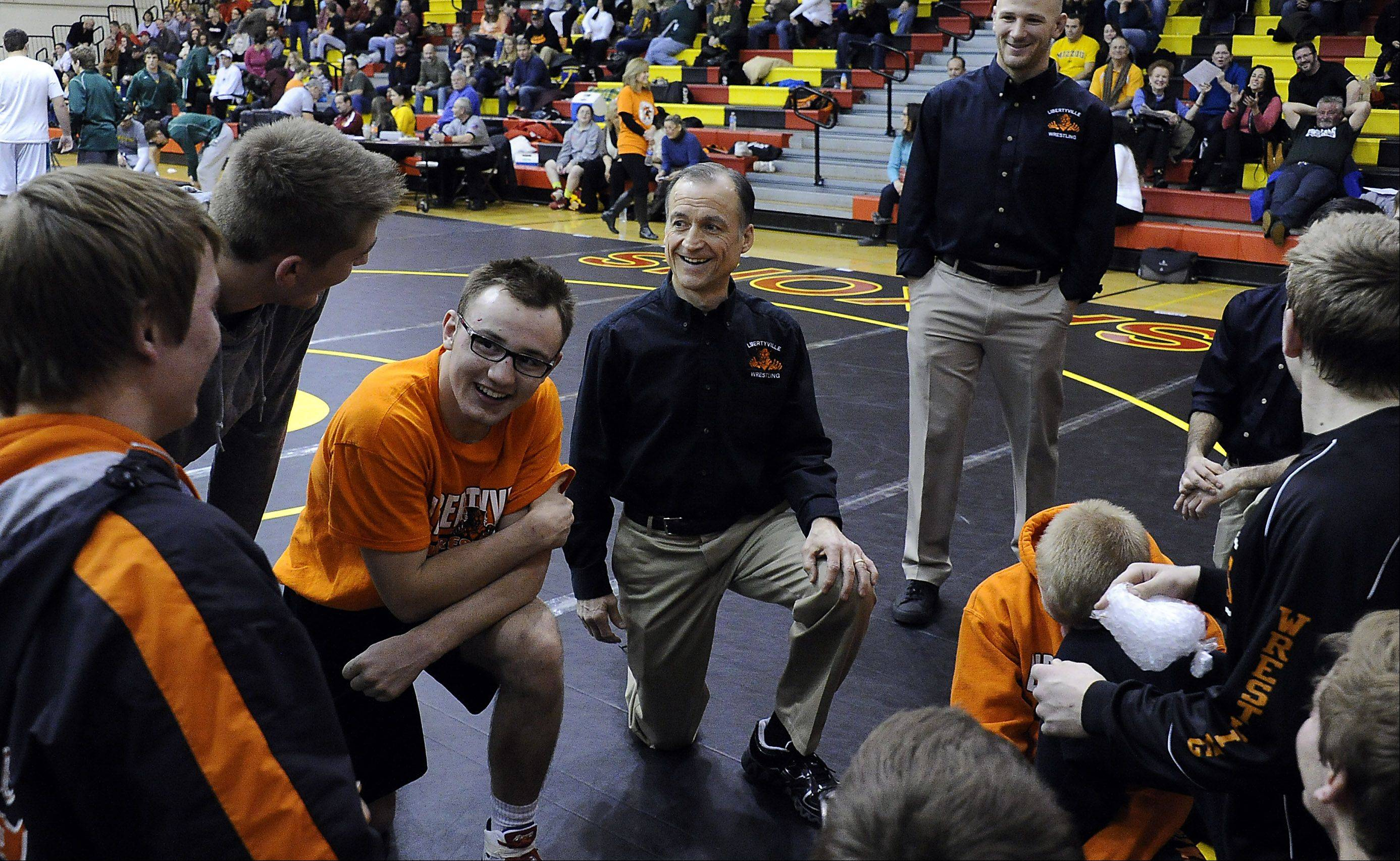 Libertyville wrestling coach Dale Eggert meets with his group after the Wildcats topped Crystal Lake South in the quad at Schaumburg on Saturday.