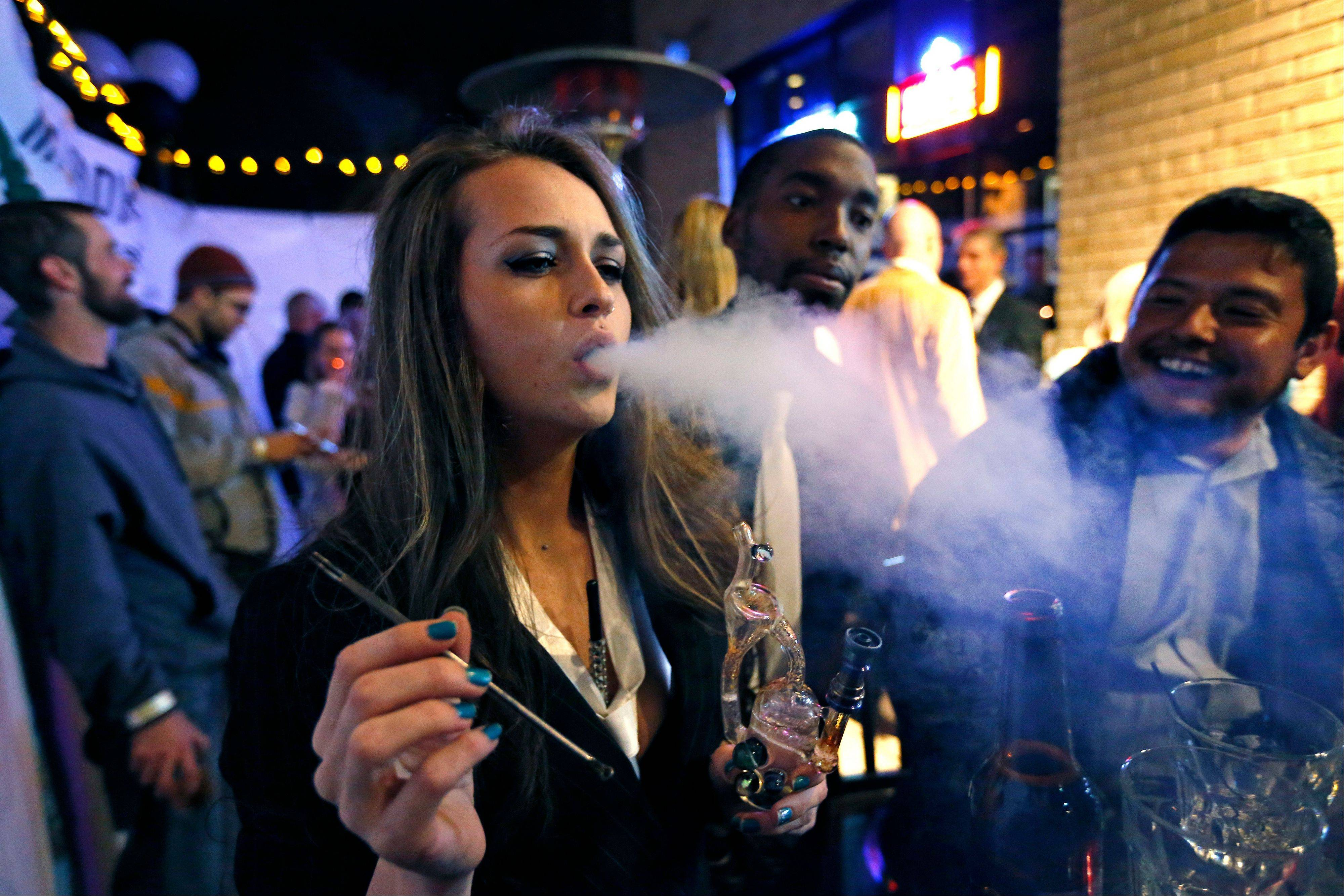 Partygoers smoke marijuana Tuesday during a Prohibition-era themed New Year's Eve party celebrating the start of retail pot sales in Denver.