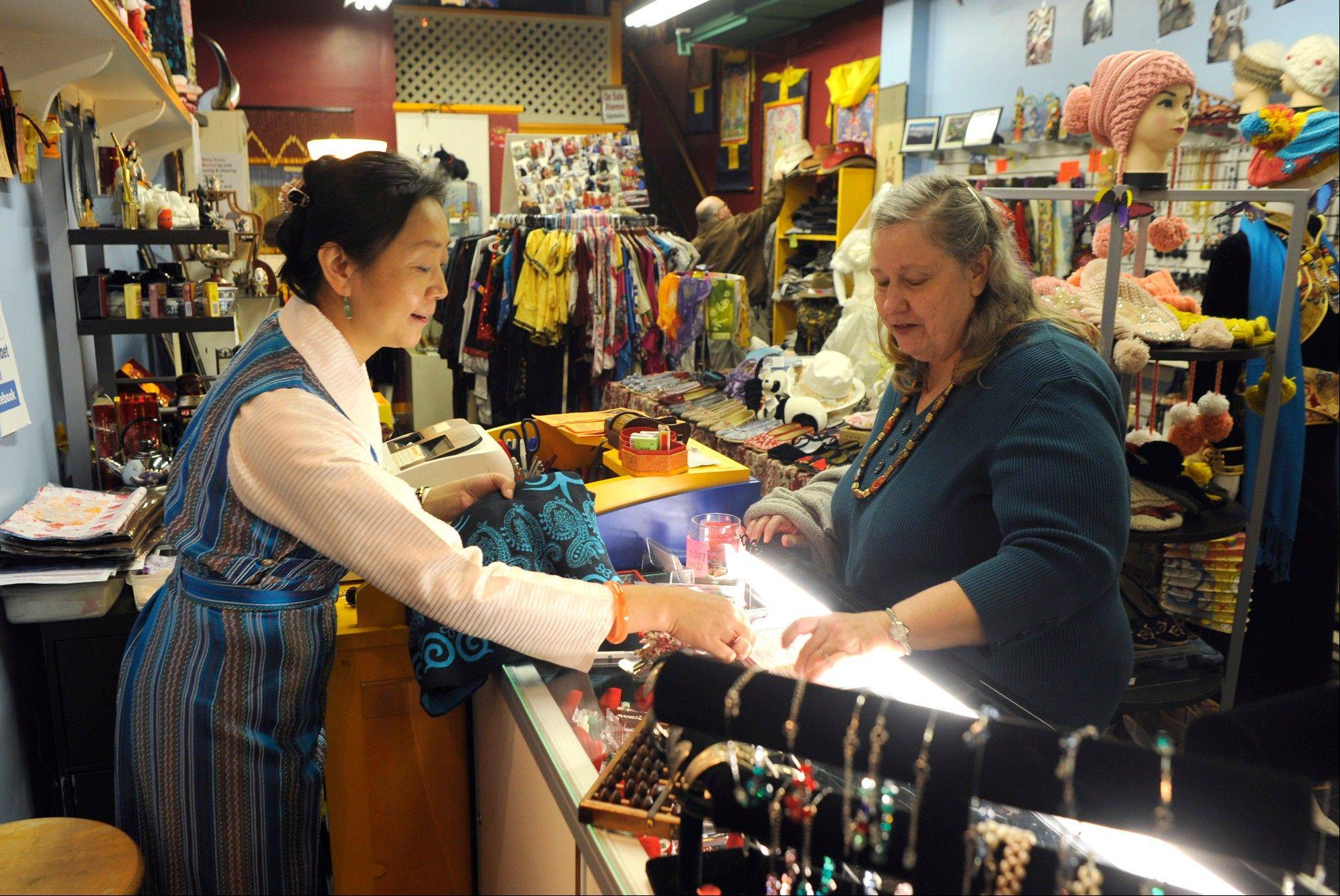 Ping's Tibet shop owner Ping Wu Longval, left, in Cotton Exchange shopping center, helps local costumer Sherry Rhodes with her shopping in Wilmington, N.C., as Rhodes is looking for ideas for wedding anniversary gifts for her husband.