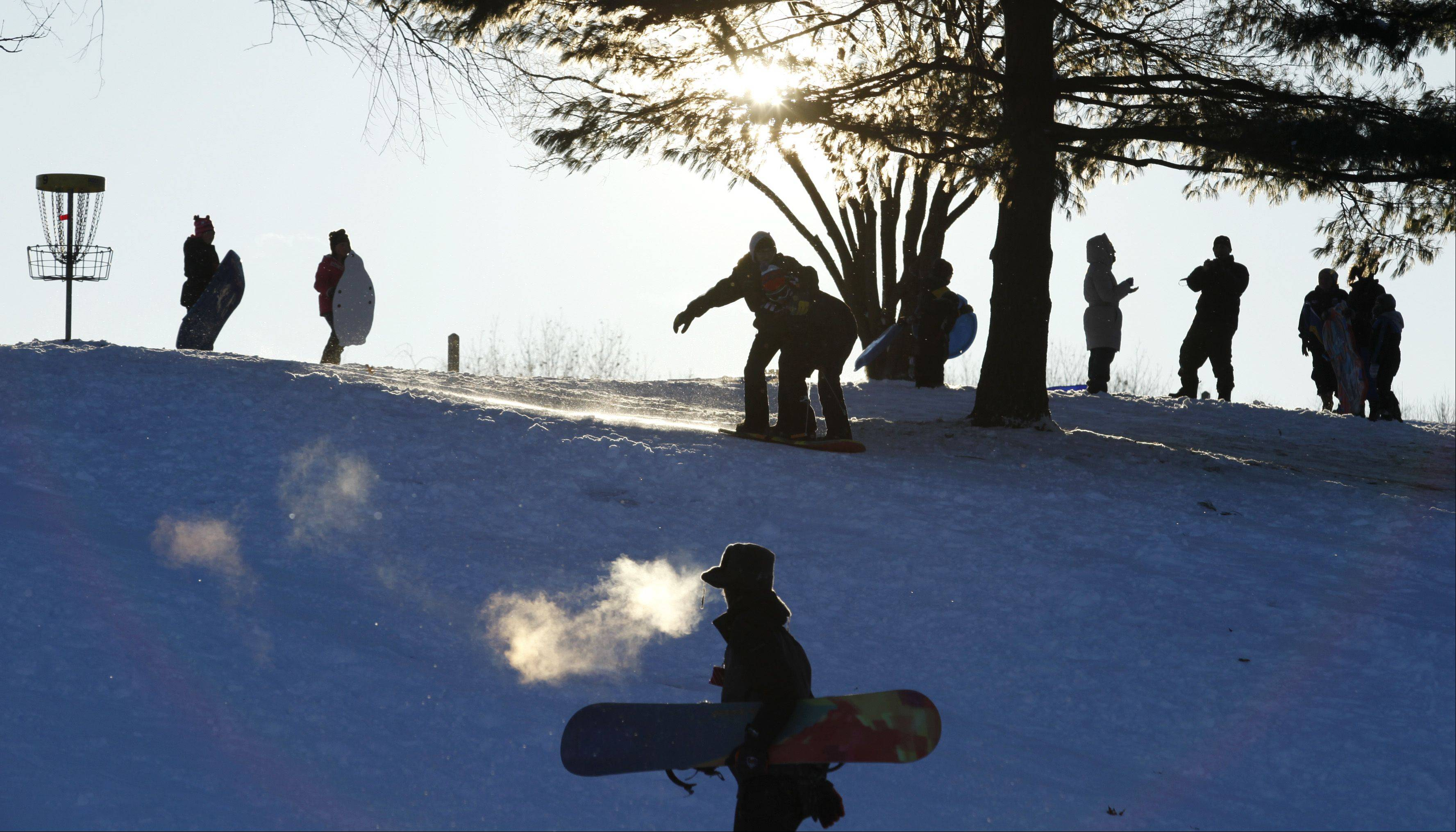 A snowboarder exhales into the frigid air as he hikes to the top of the hill Thursday afternoon at Randall Oaks Park in West Dundee. The popular sledding hill was packed with sledders, snowboarders and parents with cameras as the recent snowfall created a perfect chance to get out and play.