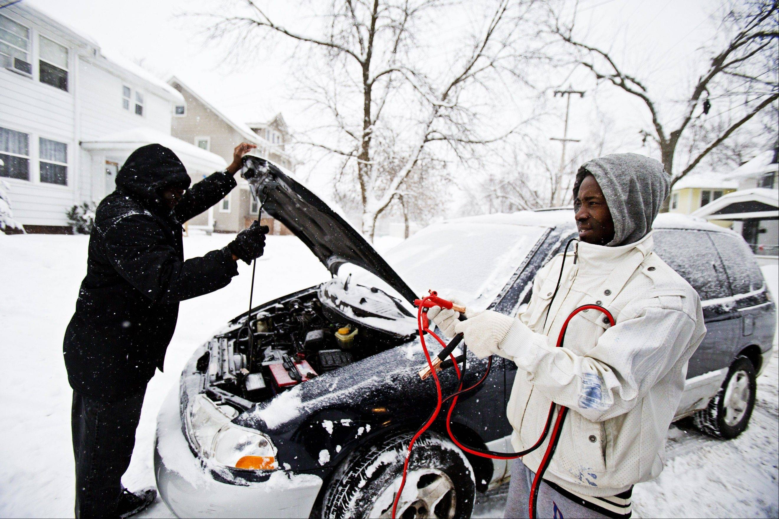 Mohamed Yusuf, right, jump starts his stepfather Mohamed Adem's car in Grand Rapids, Mich., Sunday. More snow was expected to blanket the state Sunday evening, followed by the same sub-zero cold that hit Chicago late Sunday.