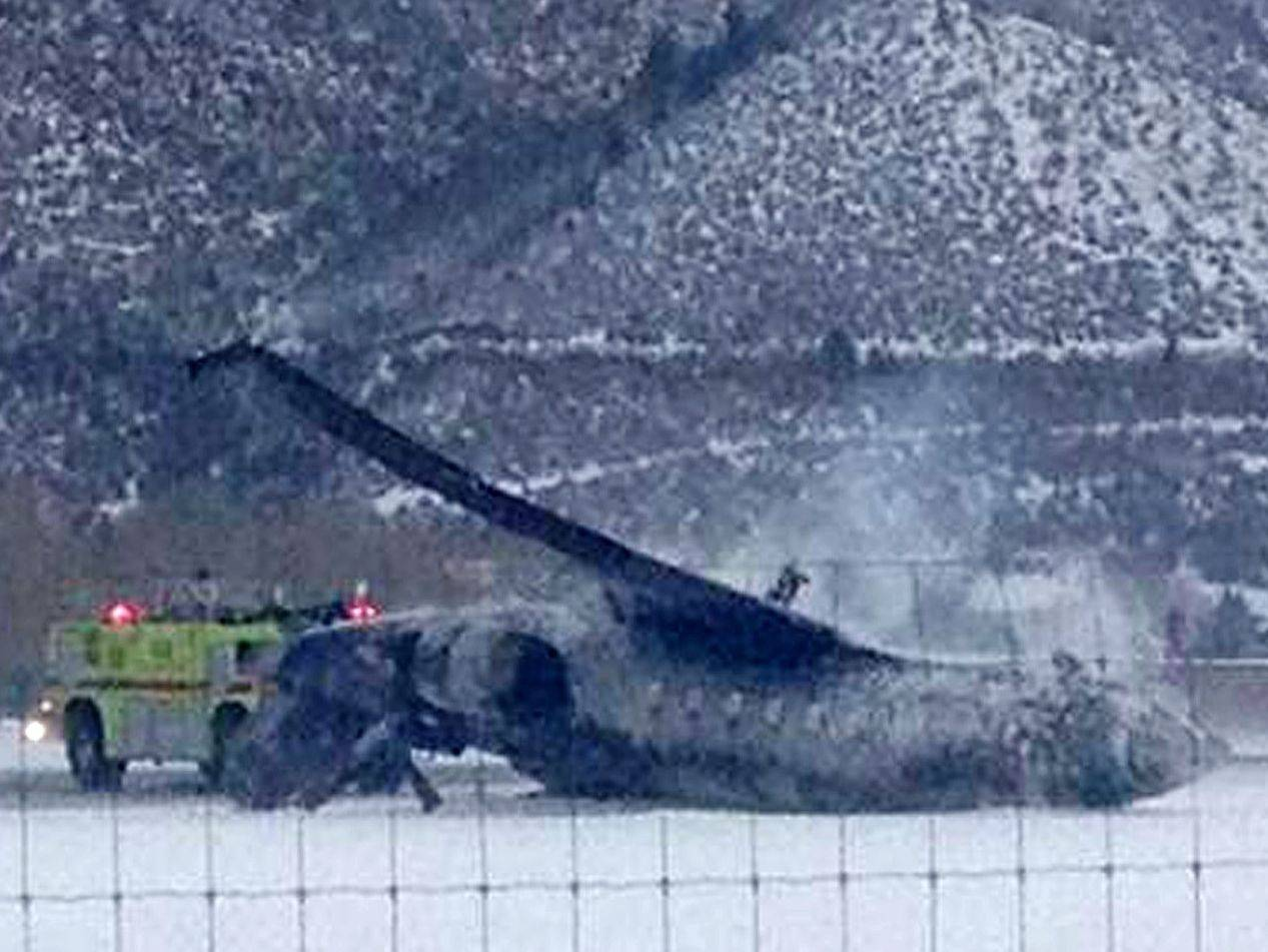 Emergency crews respond as a plane lies on a runway at Aspen Airport in Colorado after it crashed upon landing Sunday.