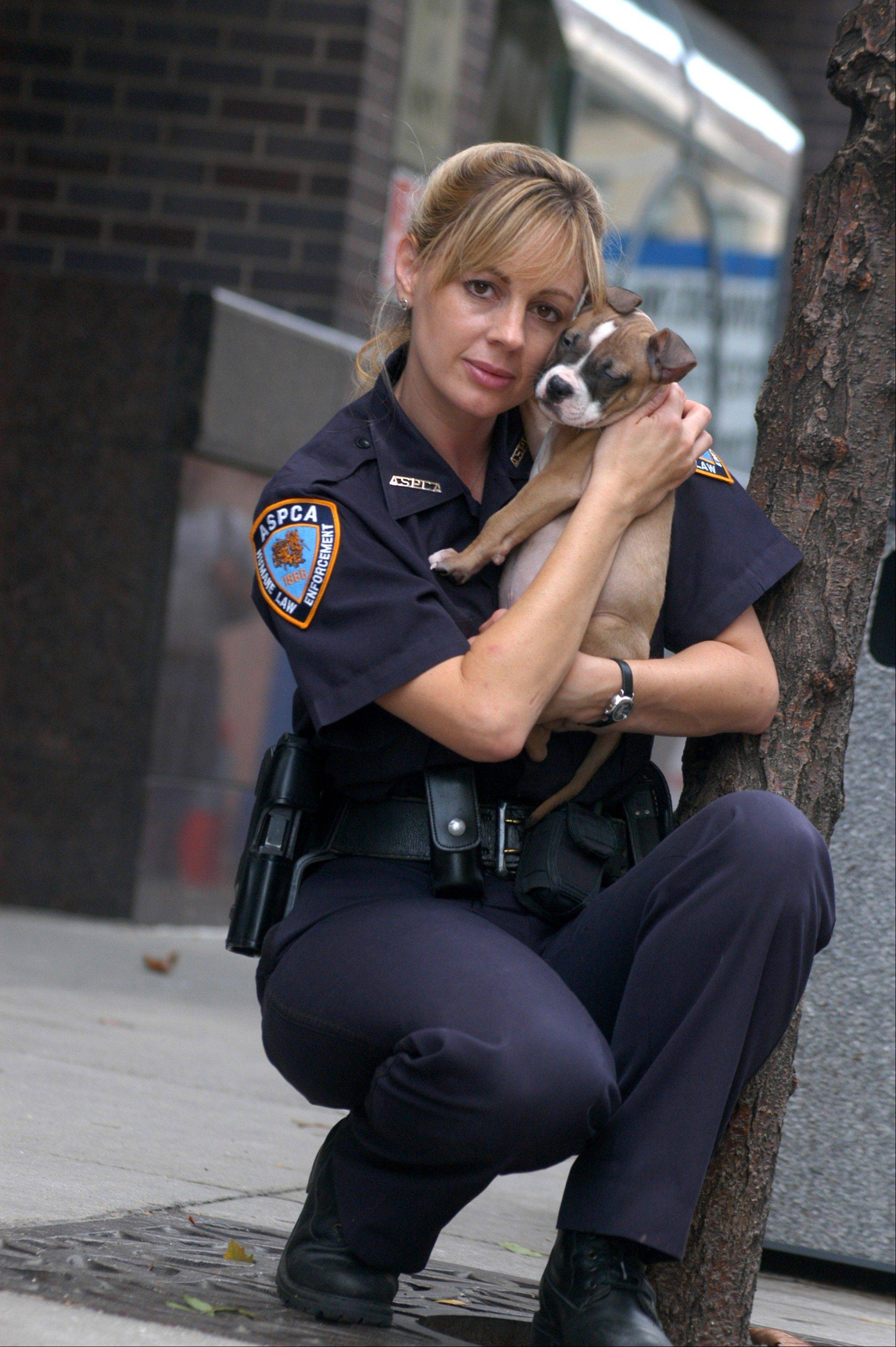 This 2004 photo provided by Animal Planet shows investigator Annemarie Lucas of the Humane Law Enforcement division of the American Society for the Prevention of Cruelty to Animals with a rescued dog in New York.