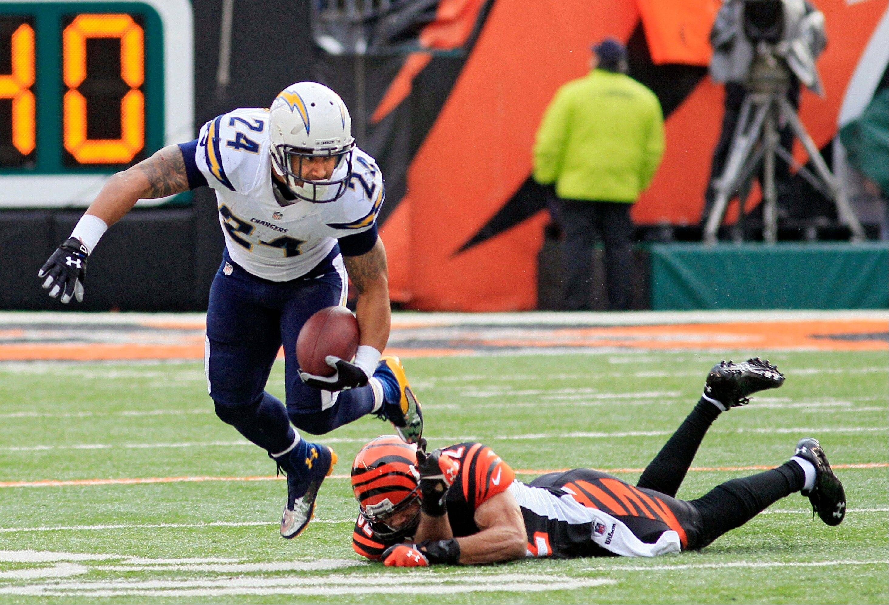 San Diego Chargers running back Ryan Mathews (24) avoids the tackle by Cincinnati Bengals safety Chris Crocker in the first half of an NFL wild-card playoff football game on Sunday, Jan. 5, 2014, in Cincinnati.