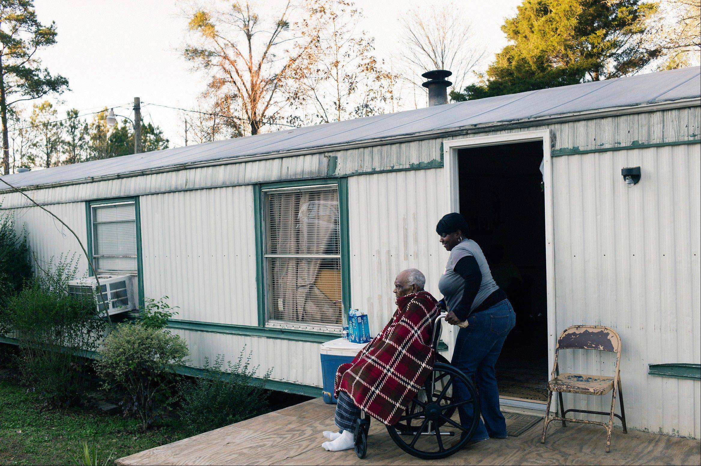 Twanda Blount helps her grandfather Chocolate Blount, 91, with his wheelchair outside their home on Dec. 18 in Pine Hill, Ala. Three years earlier, Chocolate Blount was discharged from hospice care after about a year.