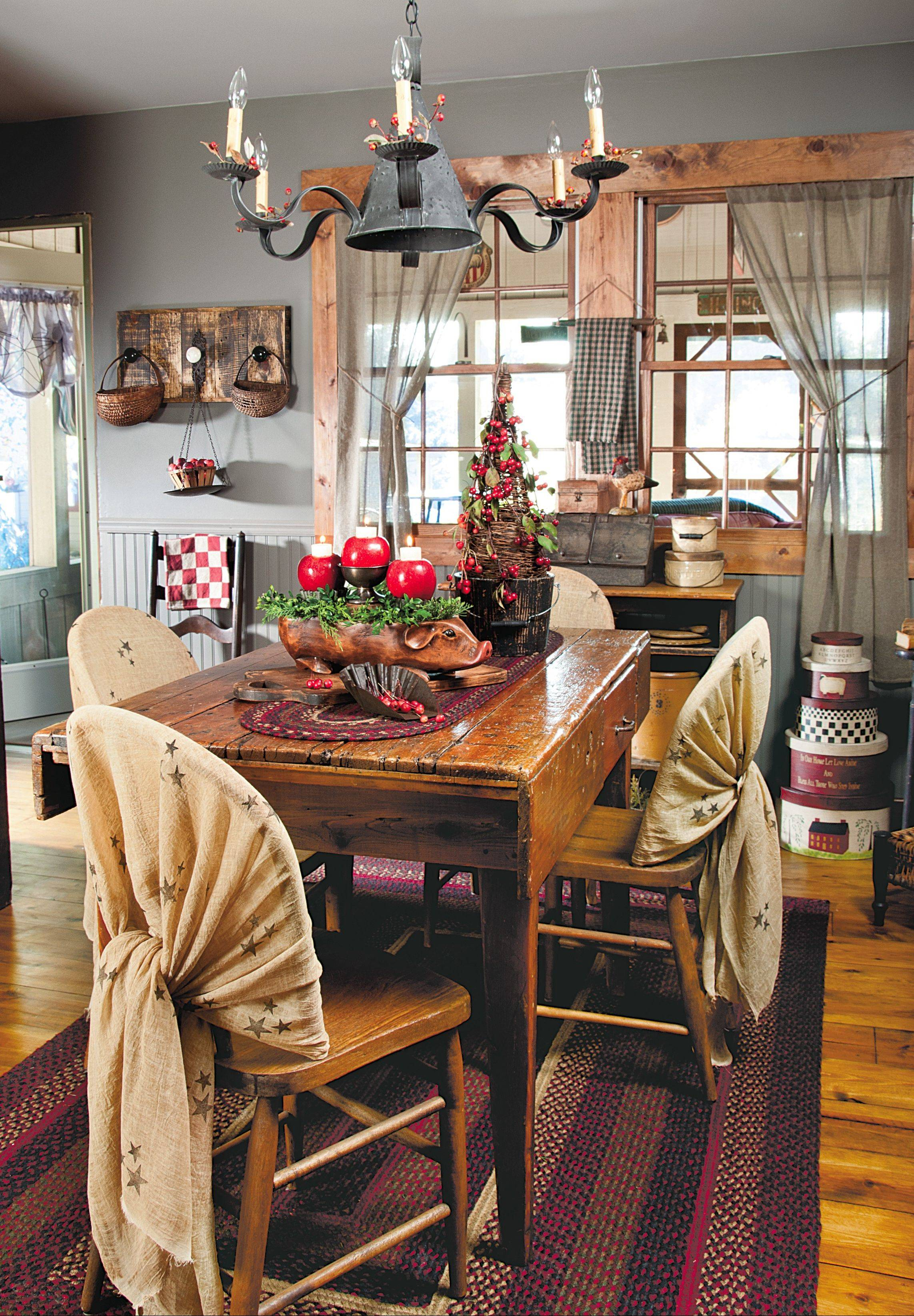 Touches of red appear on the table courtesy of apples hollowed out to hold votive candles and a scale pan holding apples near the back door repeats the tablescape's motif, while gauzy curtains let in light and gently frame rustic furnishings.