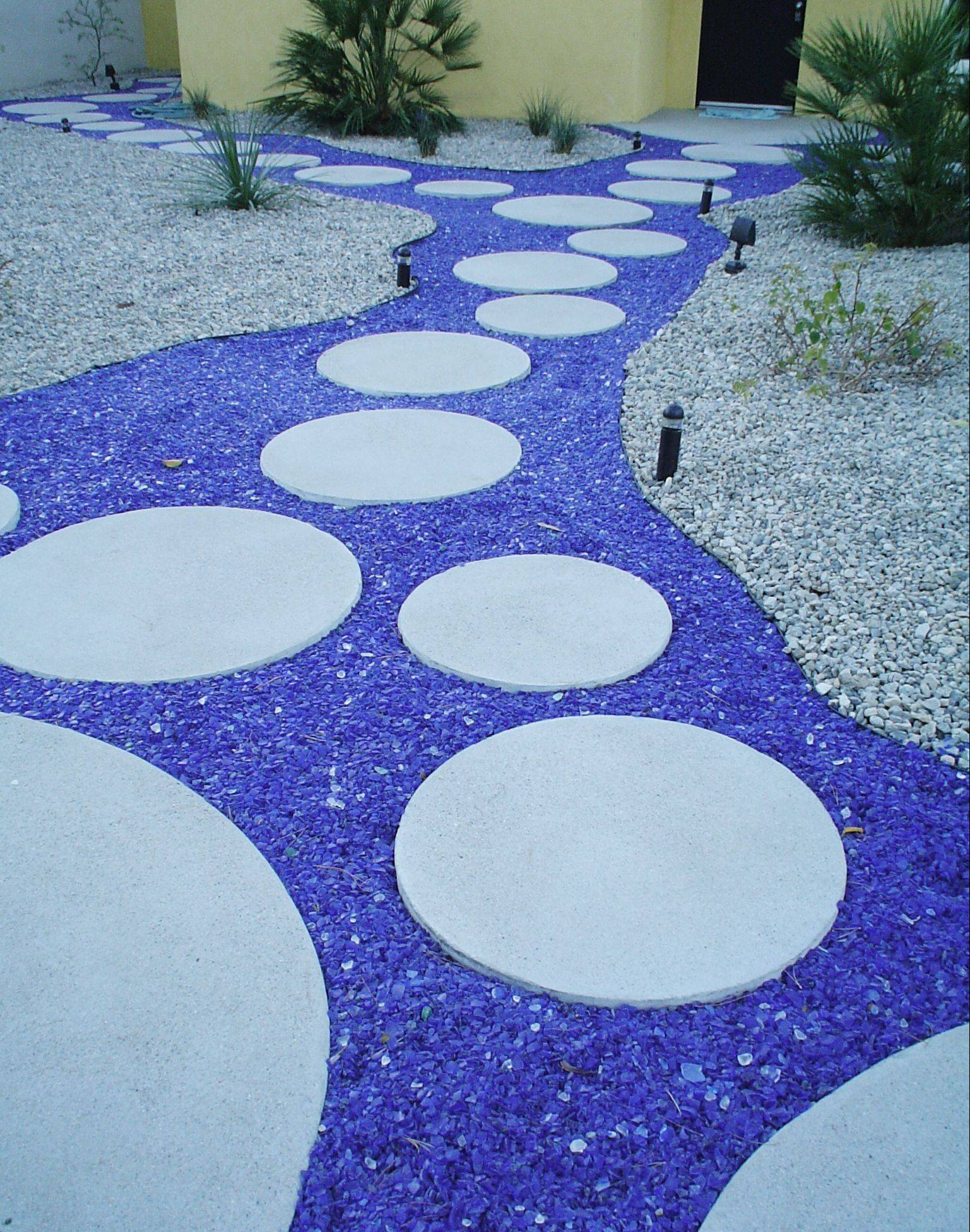 Grass isn't the only filler you can use between your steppingstones. Tumbled recycled glass, pebble mosaics, gravel and ornamental ground cover are also creative choices.