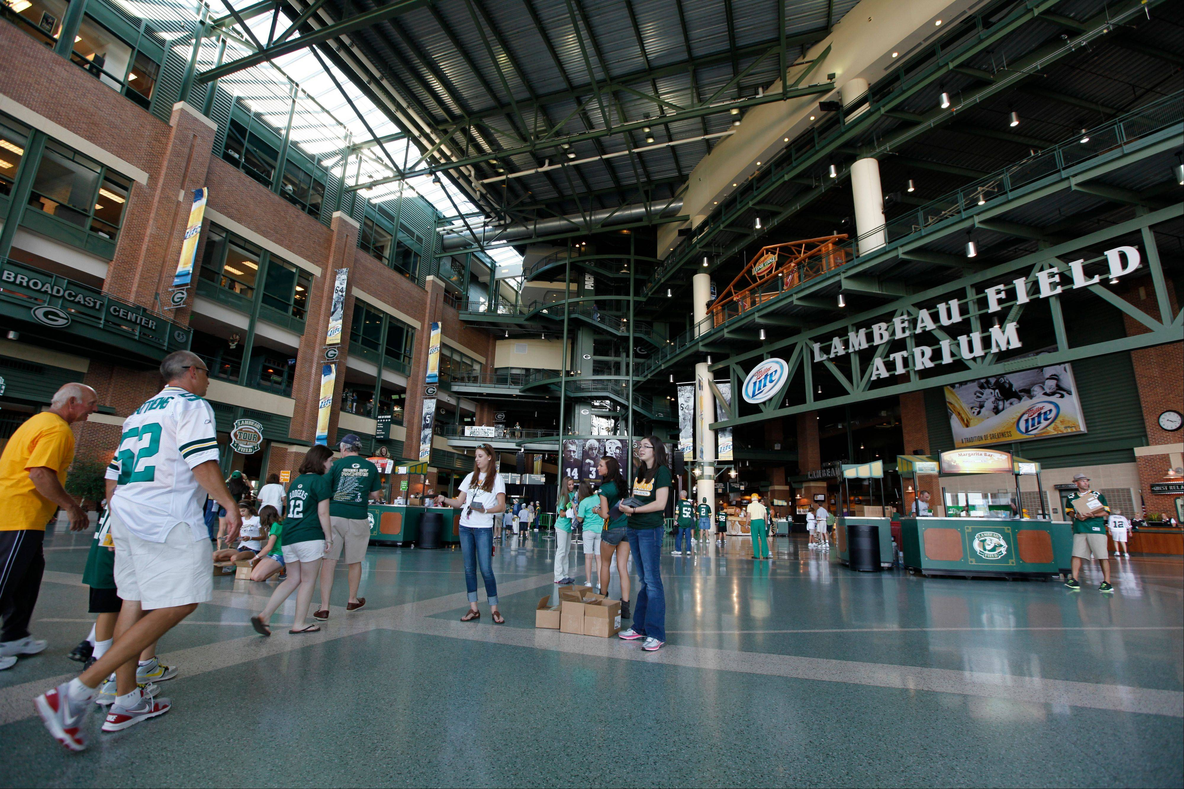 Fans walk through the atrium of Lambeau Field before an NFL preseason game in 2011. A tour of the stadium offers a peek behind the curtain where so much of professional football's history has been written.