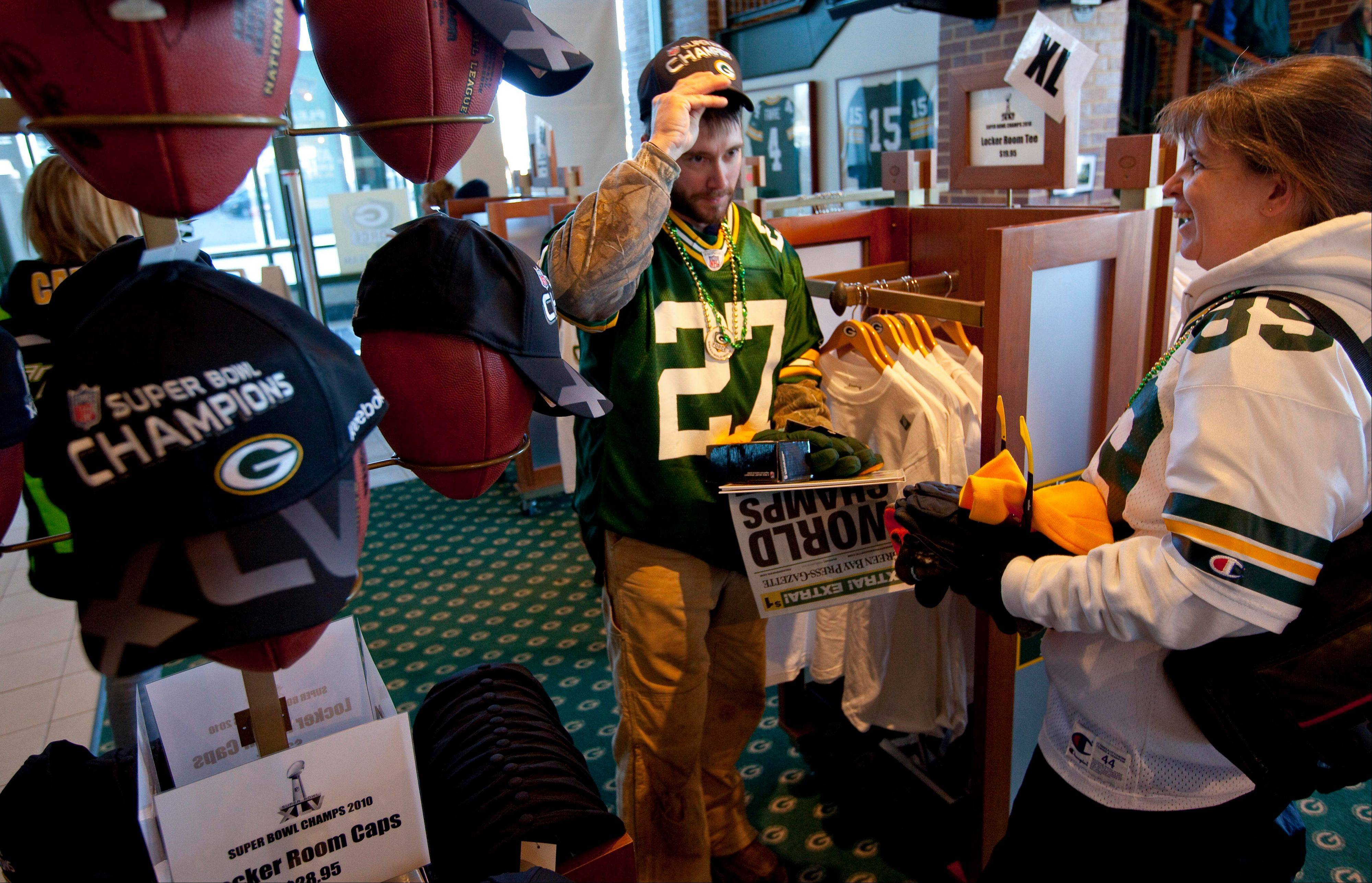 "Green Bay Packers fans Ted Lapean gets help from his wife, Jessica, in picking out a Super Bowl hat in the Packers Pro Shop prior to the ""Return to Titletown"" celebration at Lambeau Field in Green Bay, Wis."