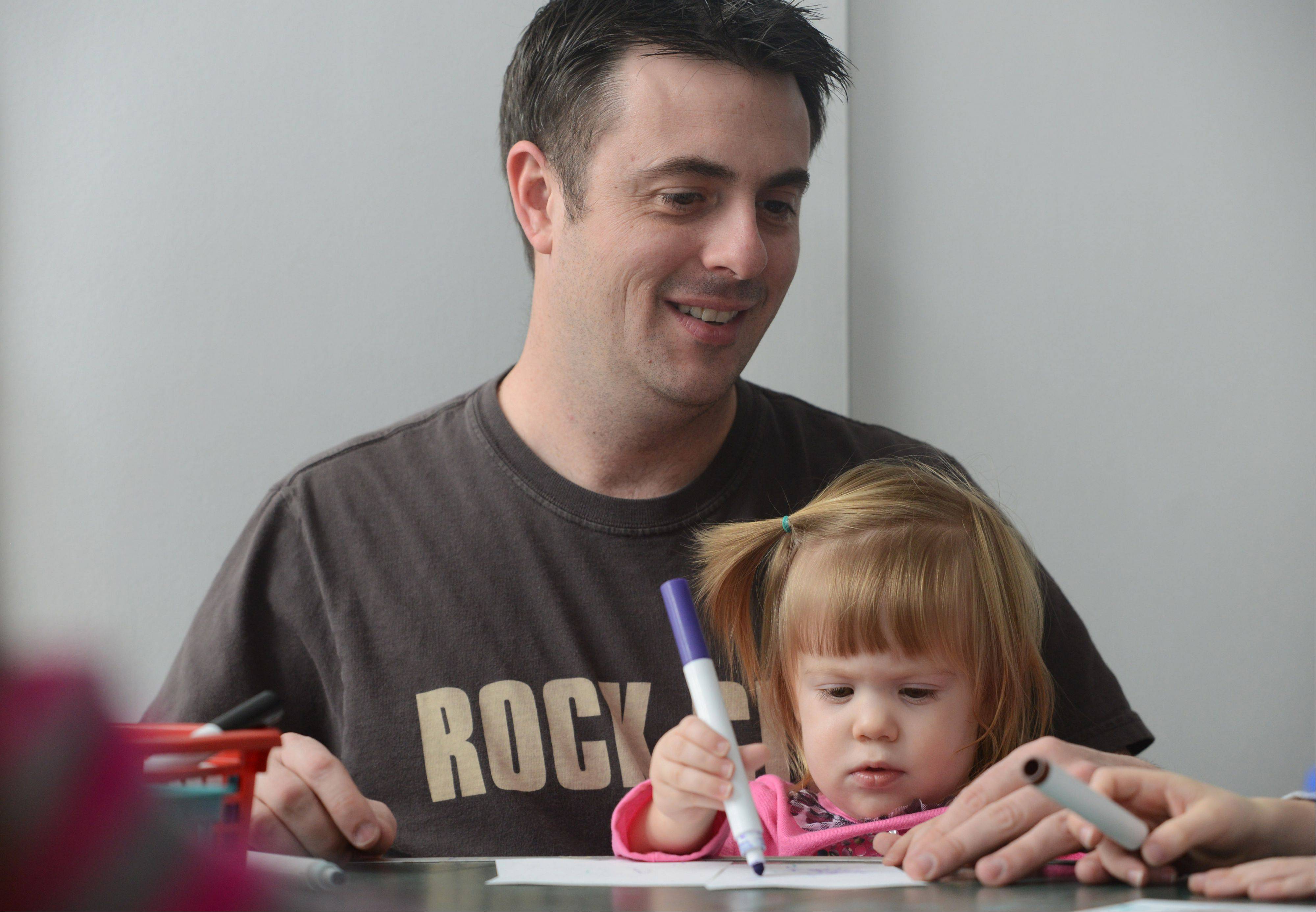Dan Volk, of Grayslake, helps his daughter Carly, 1, make a postcard during the Lake County Discovery Museum's Ring in the New Year program Tuesday.
