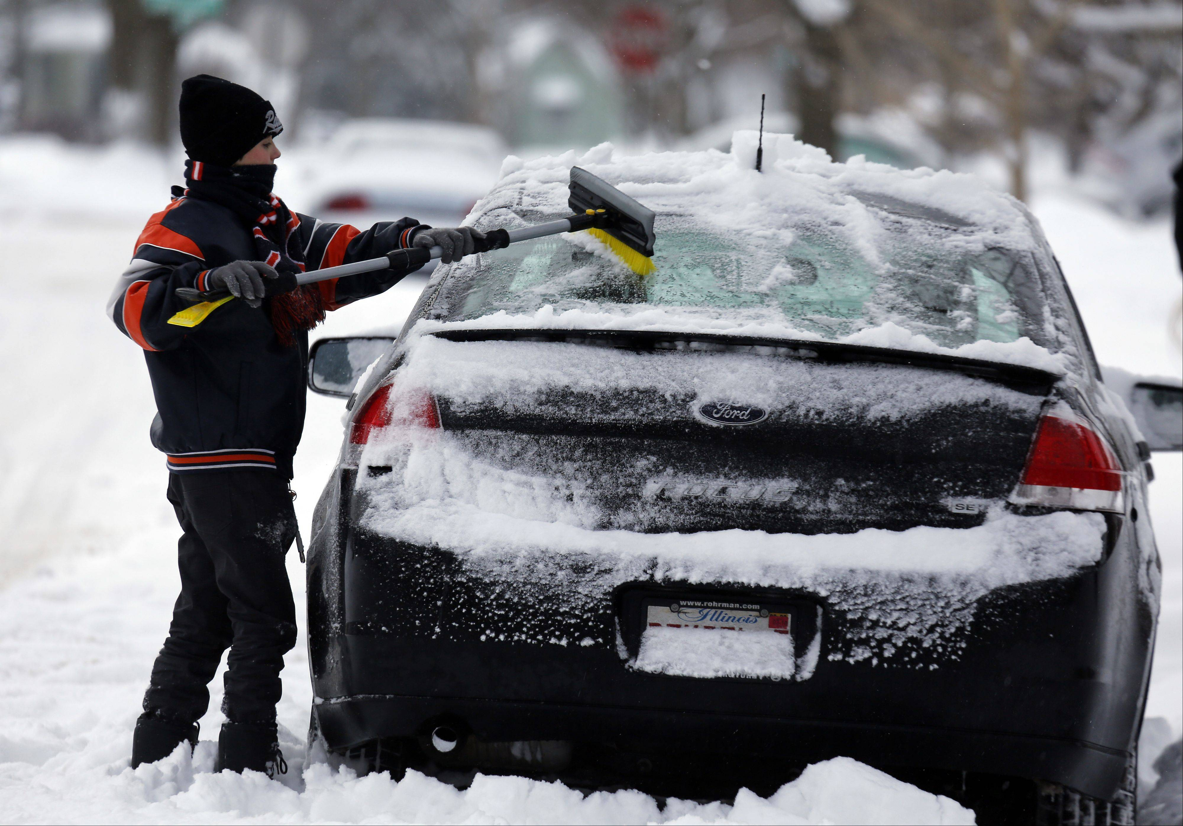 Eleven-year-old Ben Dixon, of Elgin, cleans inches of accumulated snow from the family car Thursday morning.