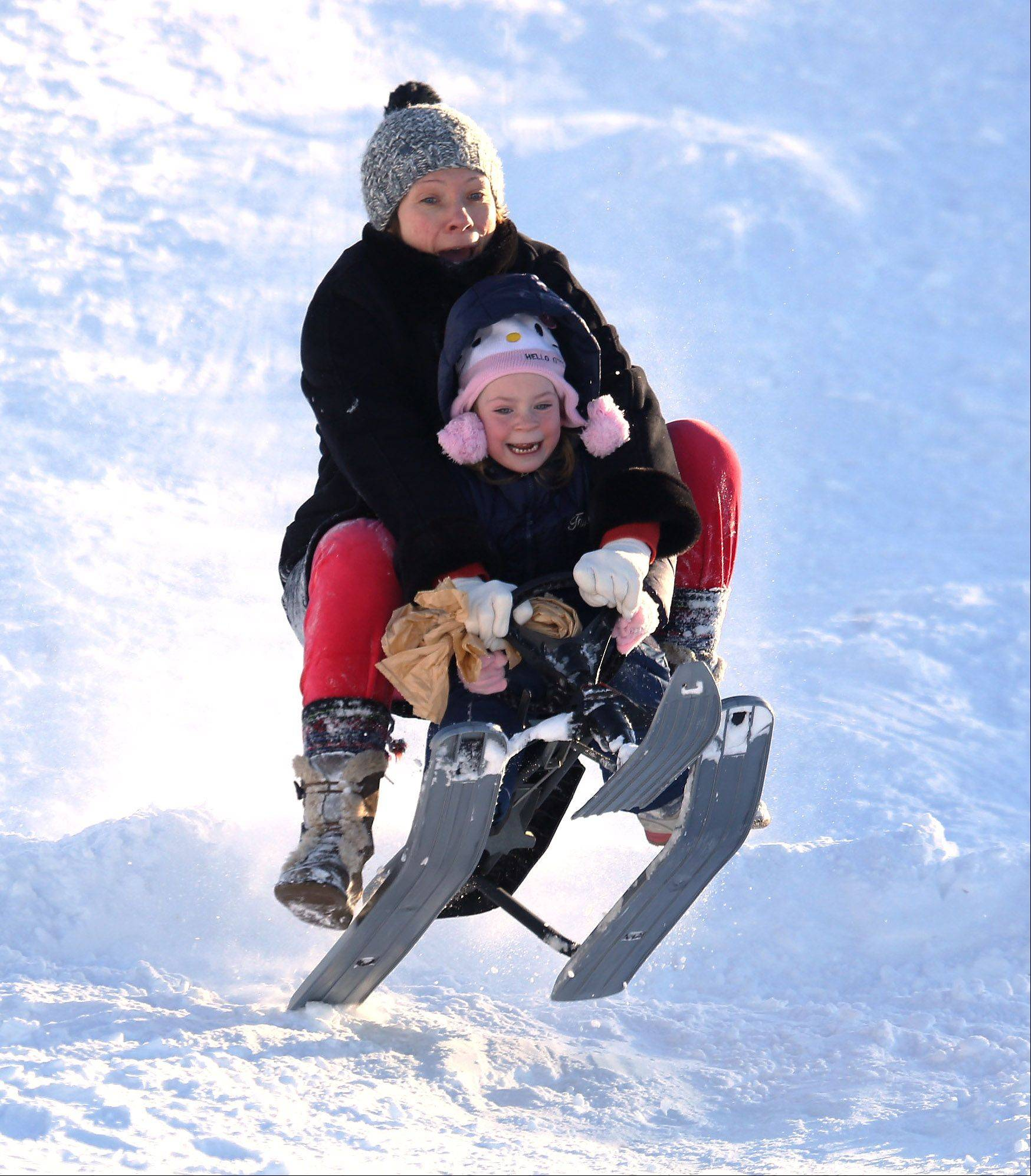 Vernon Hills residents Iriana Heyer and her daughter, Elsa, 5, sled down the hill at Century Park in Vernon Hills on Thursday after two days of falling snow produced almost 17 inches of snow. Nearly 50 people took advantage of the thick, fresh snow to enjoy the winter wonderland at the park.