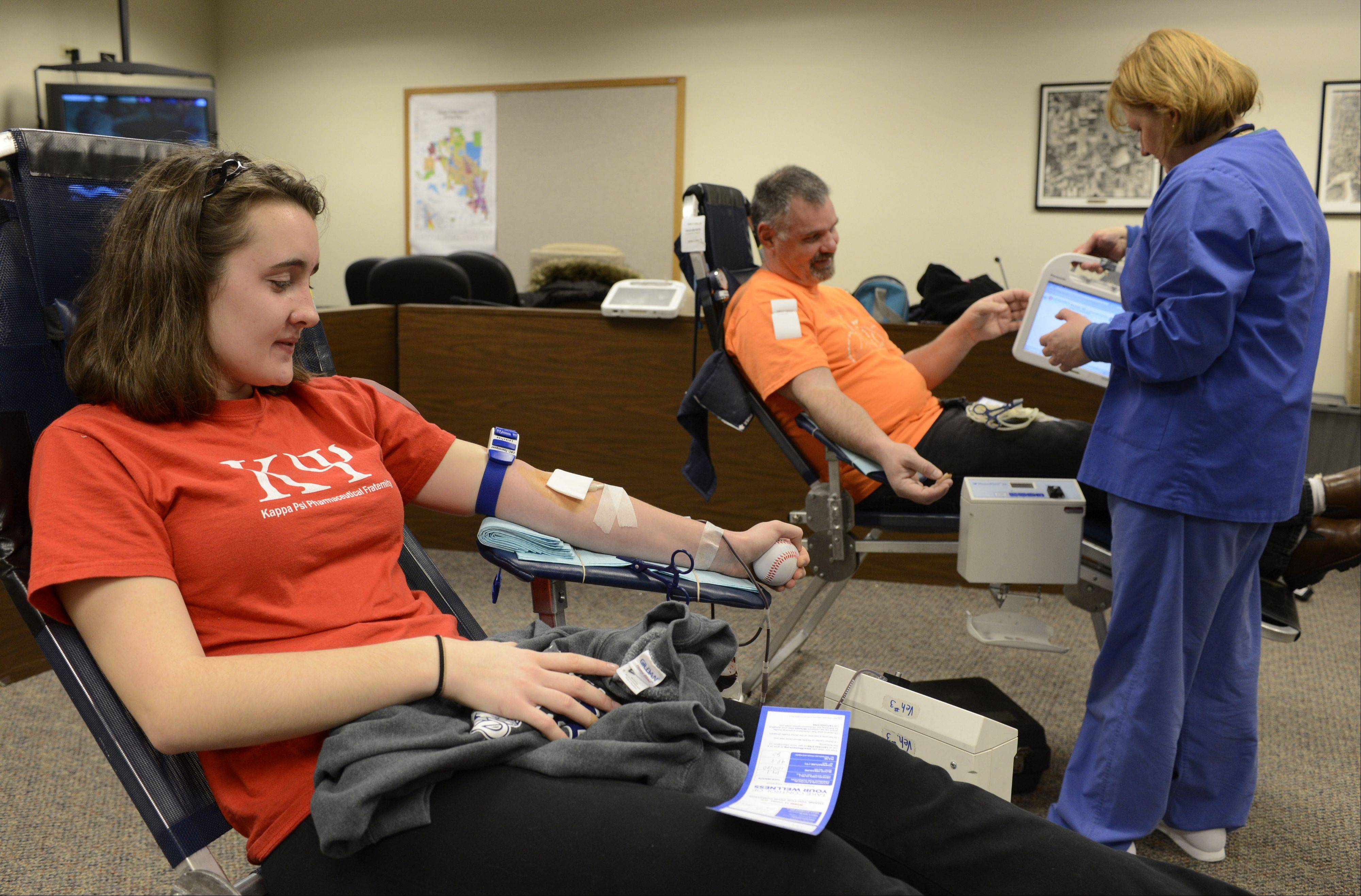 Katherine Schlebecker, of Mundelein, and her dad, Al, have their blood drawn by Malgorzata Koston of Lifesource during the Everyday Heroes winter blood drive, which also included a Salvation Army Coat and Household Goods Drive, at the Mundelein Fire Station Number One, 1000 N. Midlothian Road, Saturday.