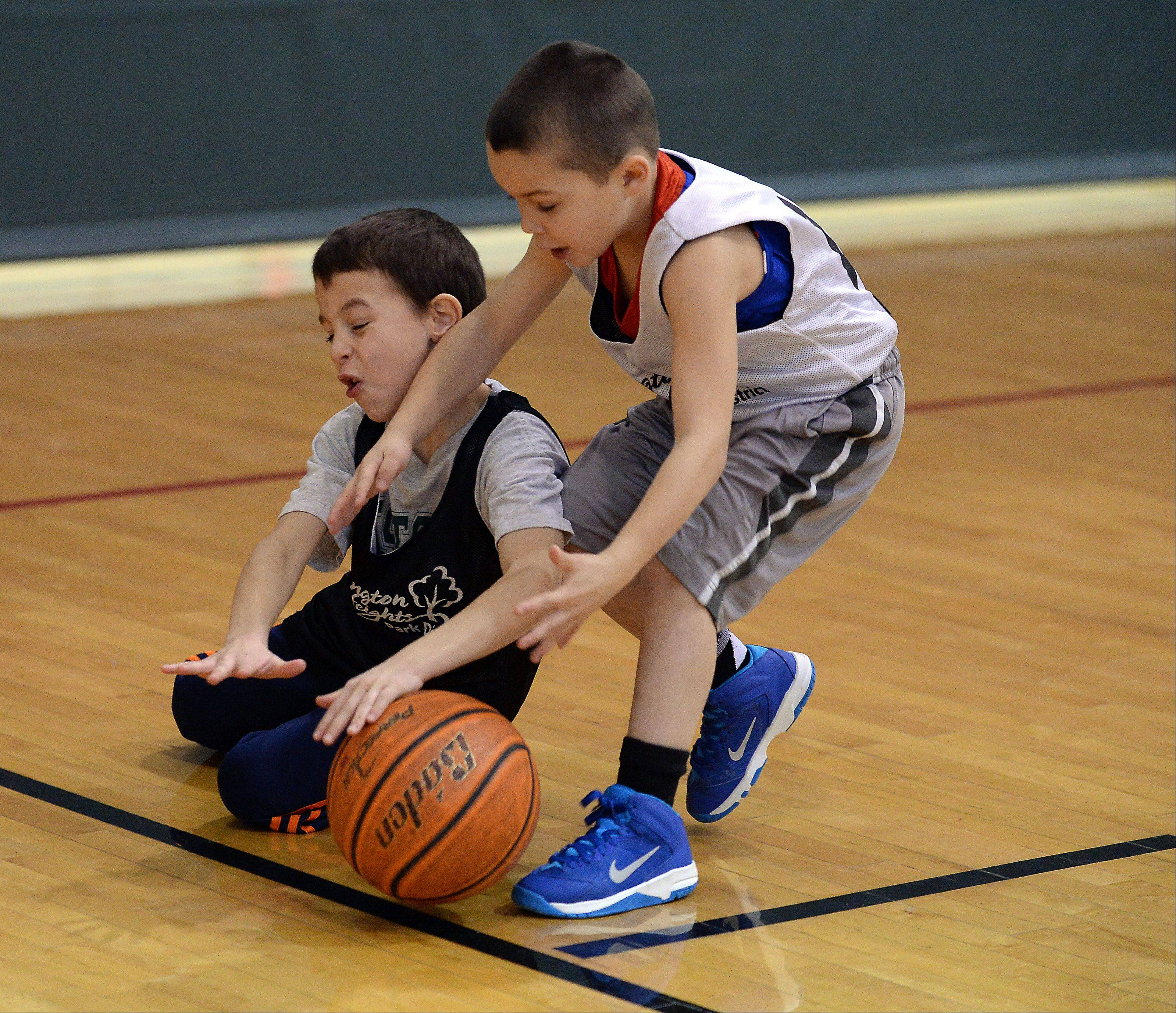 Cole Repak, 7, of the team the Lightning Boys, left, chases down a loose ball with Reid Olson, 6, of the Bulls team, during the Arlington Heights Park District 3 on 3 basketball tournament played at Pioneer Park on Saturday.
