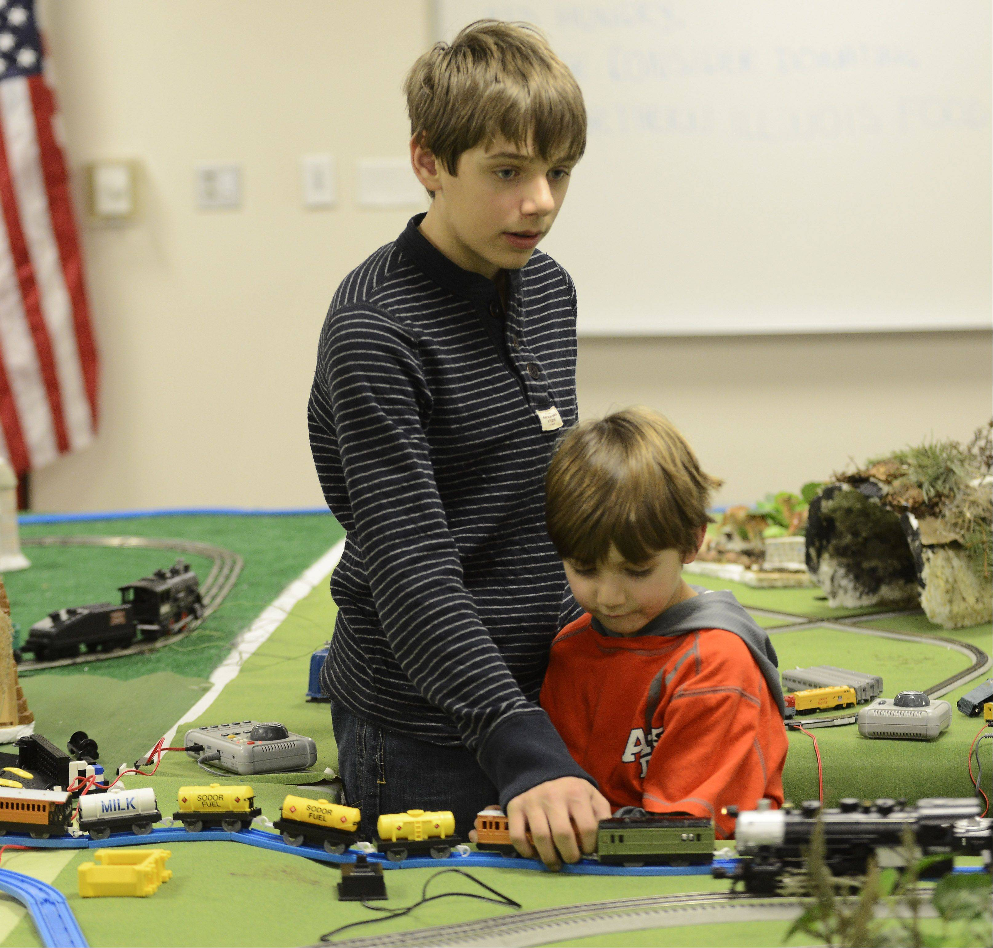Omar Rasidagic, 12, of Grayslake, stands with his brother Hamza, 5, as he displays his multiple-scale train layout during the Winter Wishes on the Railway event at Cook Park Library in Libertyville Saturday. Nonperishable food items were collected as admission, and will be donated to the Lake County Food Pantry.