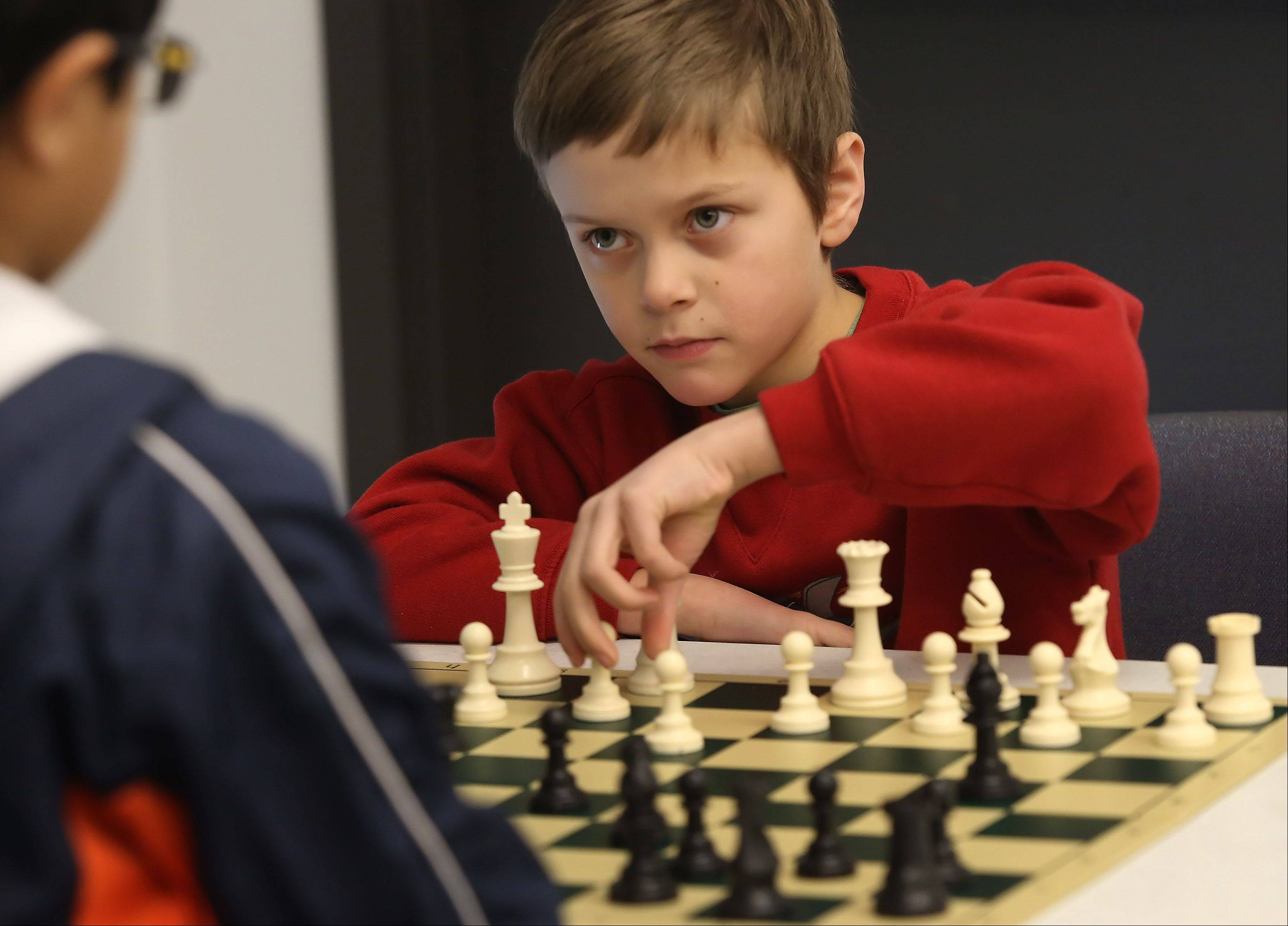 Eight-year-old Jacob Moodhe, of Buffalo Grove, makes his move during the Sixth Annual Chess Tournament on Sunday at the Indian Trails Public Library in Wheeling. The tournament was organized by the Renaissance Knights Chess Foundation for players of all ages and skill levels.